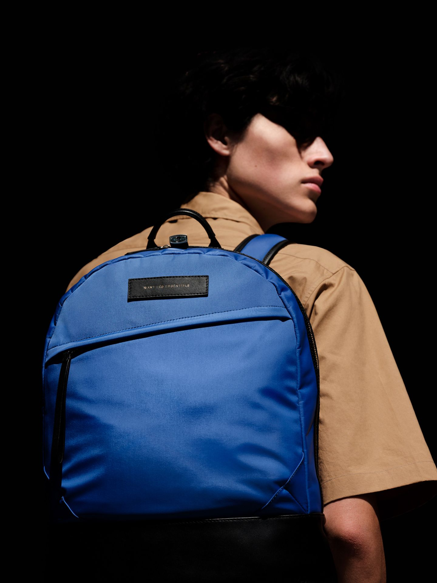 model wearing beige shirt and bright blue backpack photographed by Alexi Hobbs for Want Les Essentiels pre-Autumn Winter 2019 collection