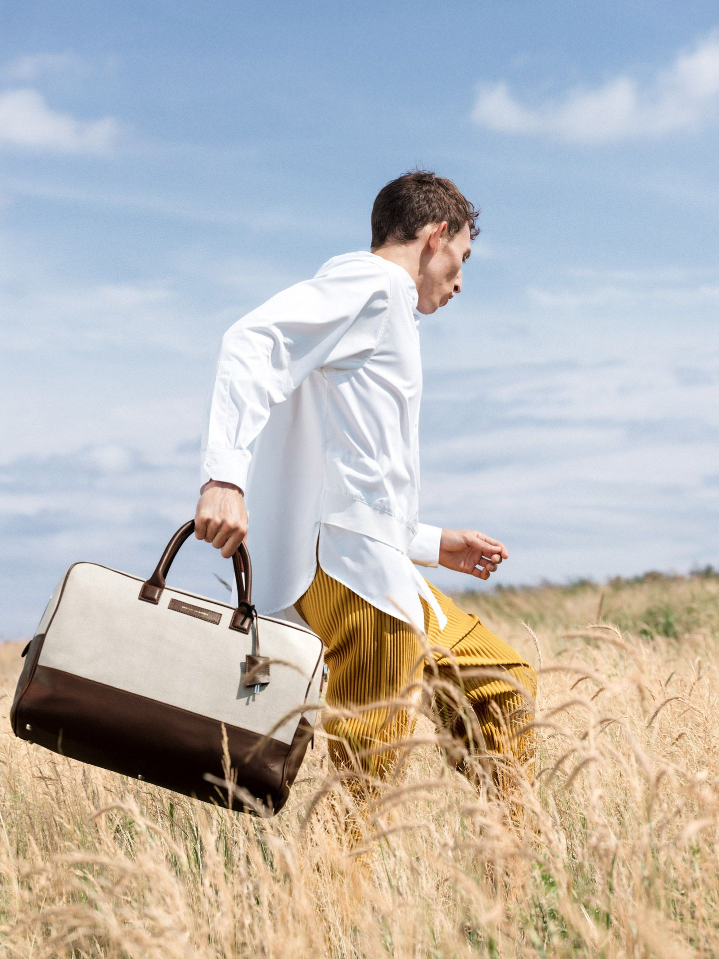 man walking in field holding bag photographed by Alexi Hobbs for Want Les Essentiels Spring Summer 2019 collection