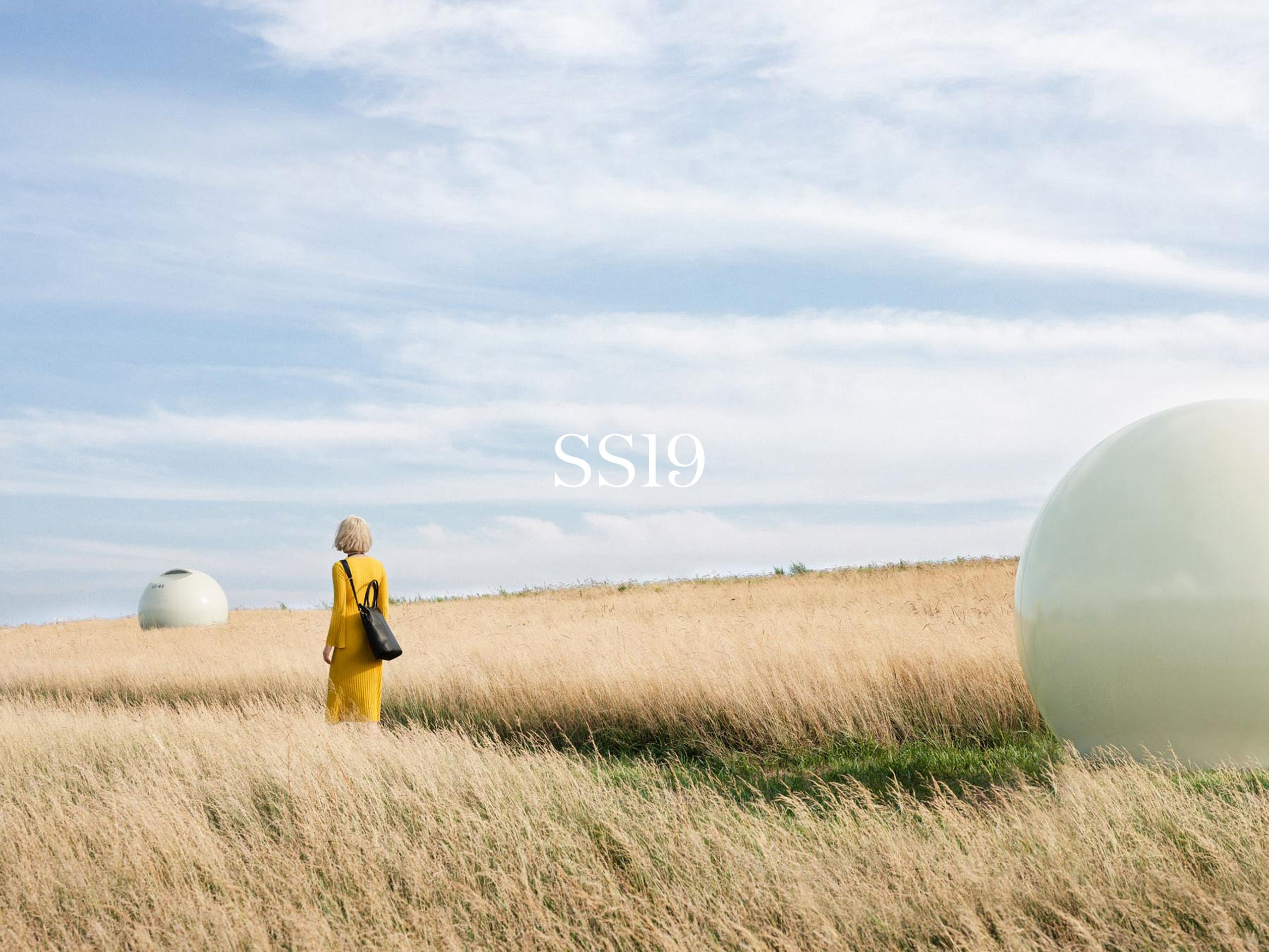 asian woman model walking in field wearing yellow dress photographed by Alexi Hobbs for Want Les Essentiels Spring Summer 2019 collection