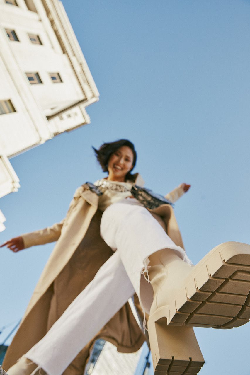 Picture of a woman wearing white boots taken from below