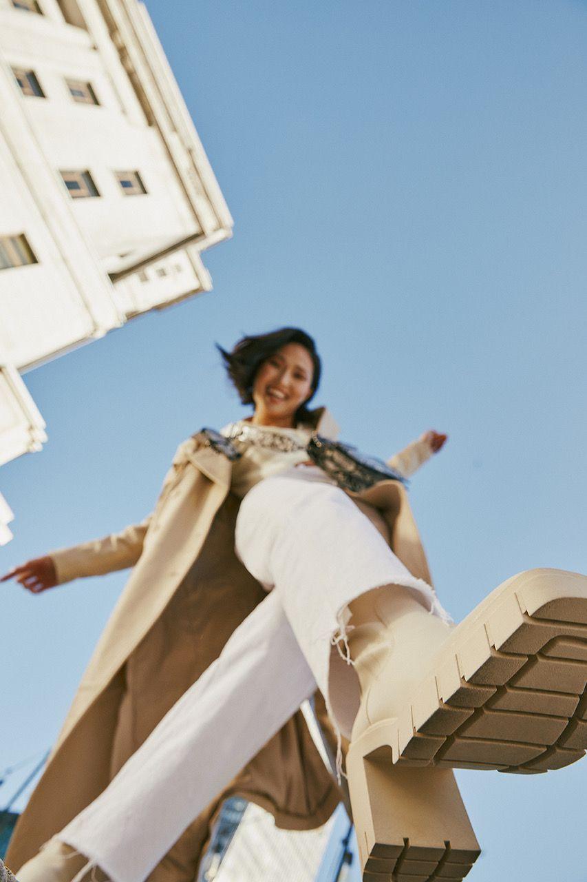 Photo en contre plongée d'une femme portant des bottes blanches