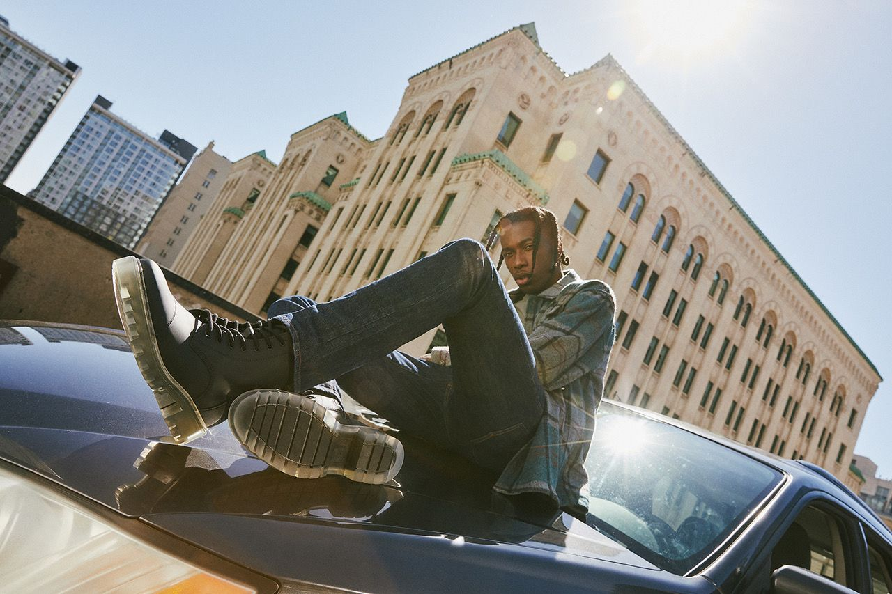 Picture of a black model posing with aldo shoes on a car on a sunny day