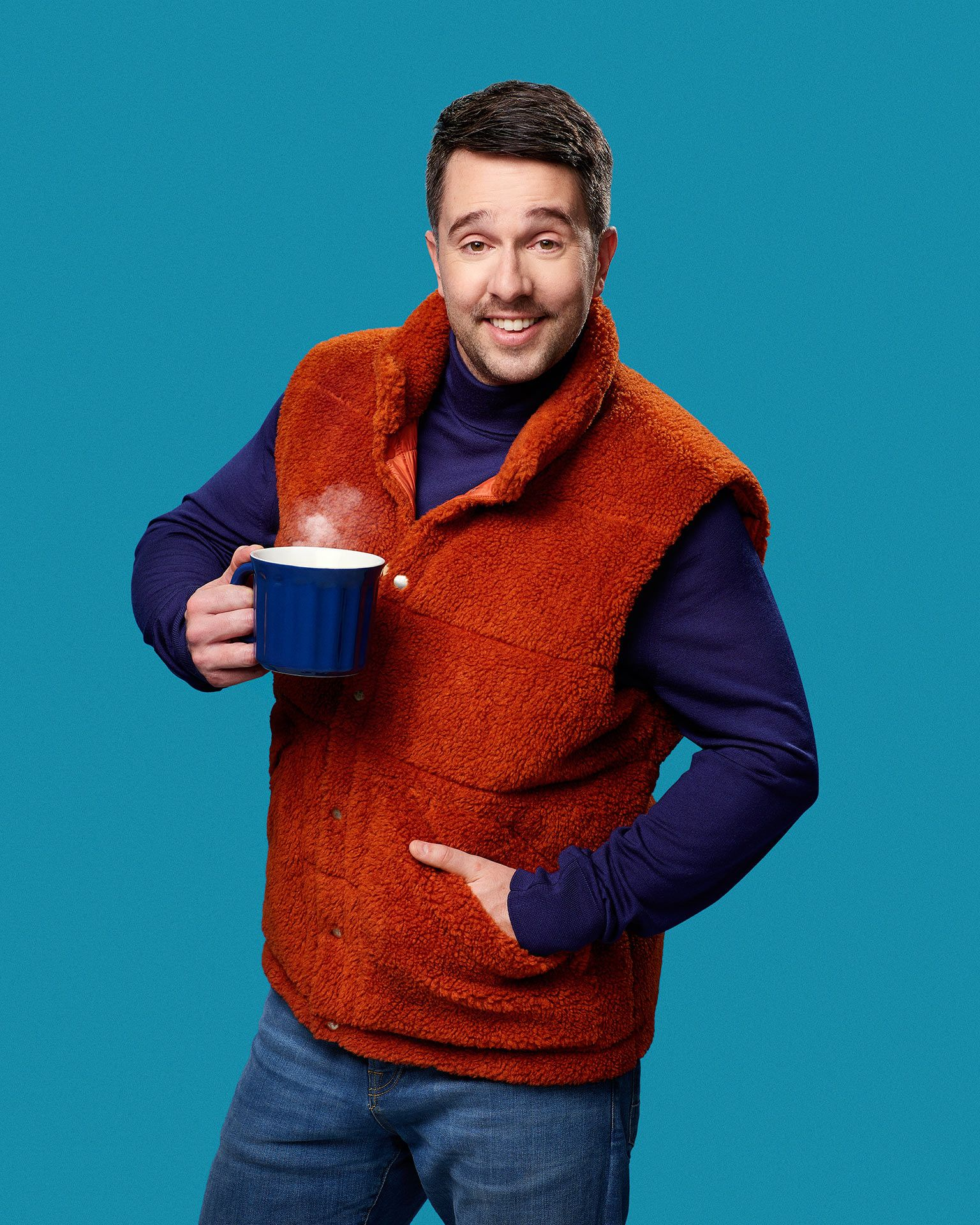 picture of humorist Alexandre Barrette dressed awkwardly in purple sweater orange armless vest mug in hand for show semi-croquant by Jocelyn Michel