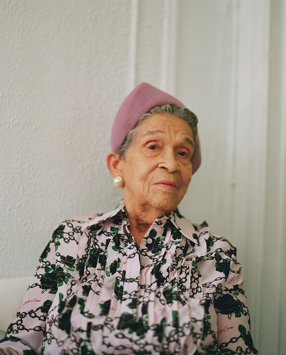 portrait of Altagracia De Pena wearing lilac headband looking at camera by Oumayma B Tanfous for Surviving the time of the butterflies with Phosphenes Magazine