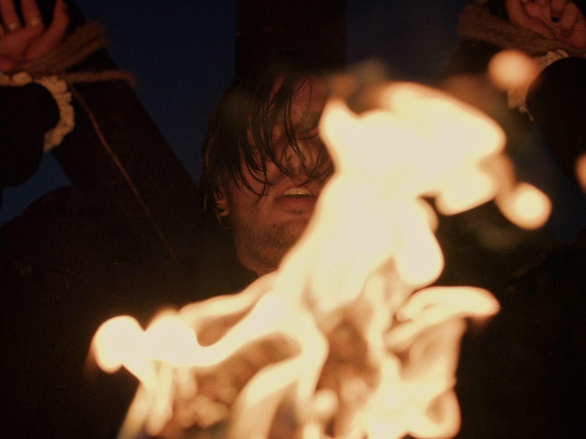 Apashe crucifié avec une torche devant son visage