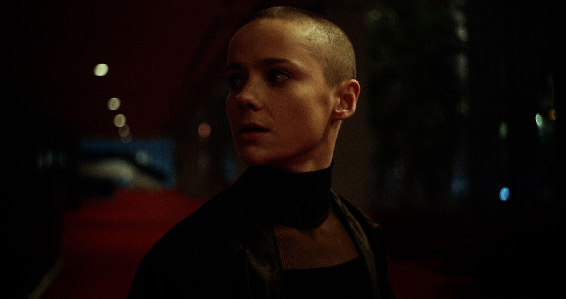 Gros plan sombre de la danseuse du vidéoclip avec un crâne rasé.