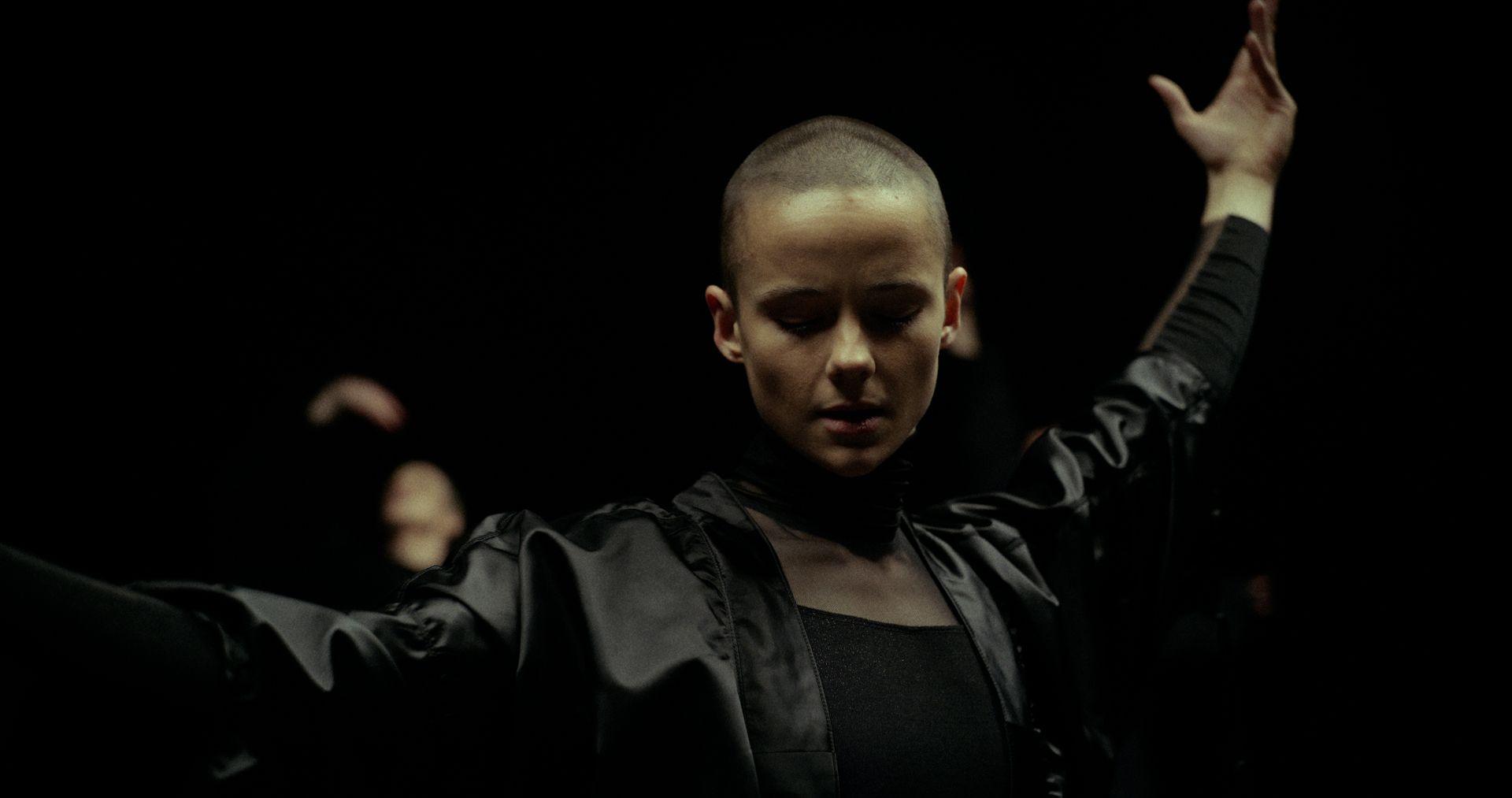 Vidéoclip de danseuse commençant sa performance avec un bras en l'air.