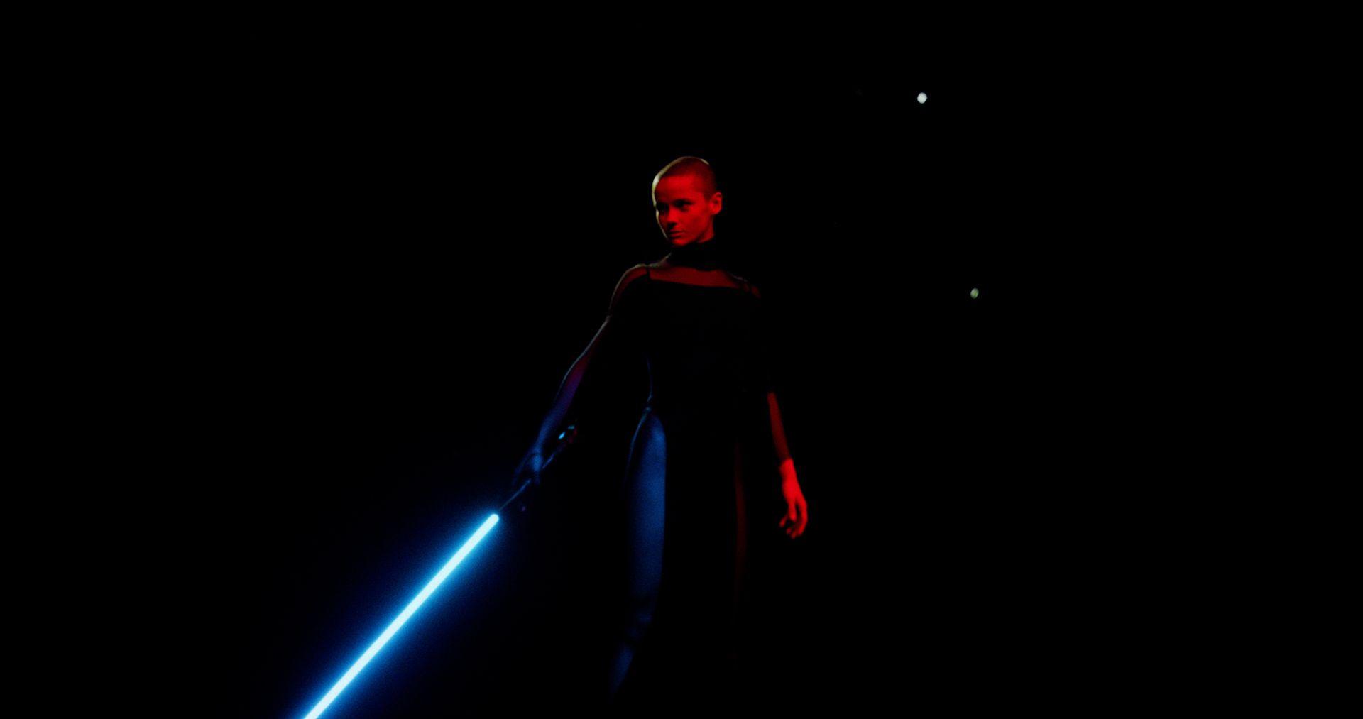 Arrêt sur image de danseuse tenant un sabre laser sur le point de commencer le combat.