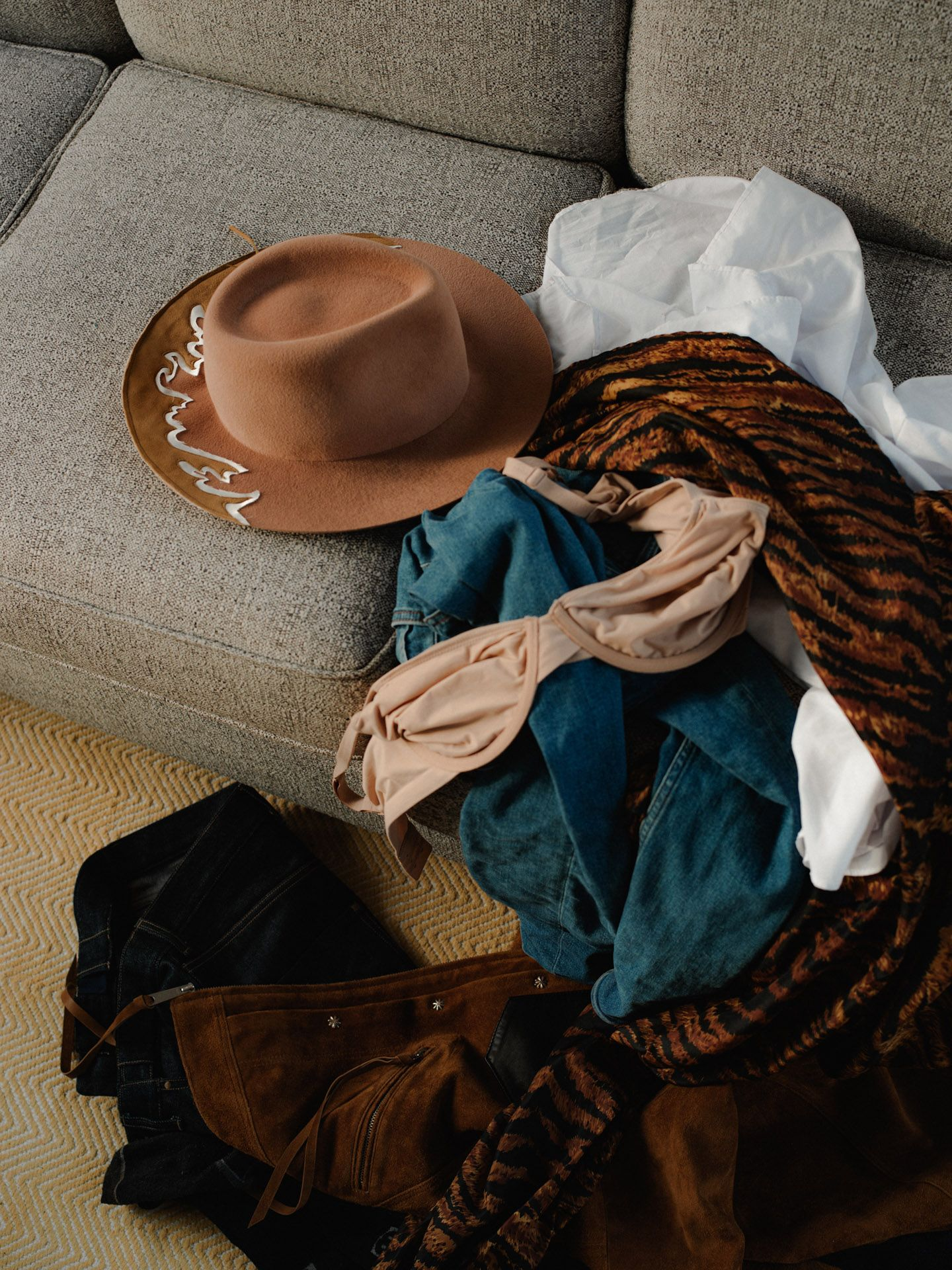 pile of clothes on couch with cowboy hat by Alexi Hobbs in St-Tite for LArose Paris