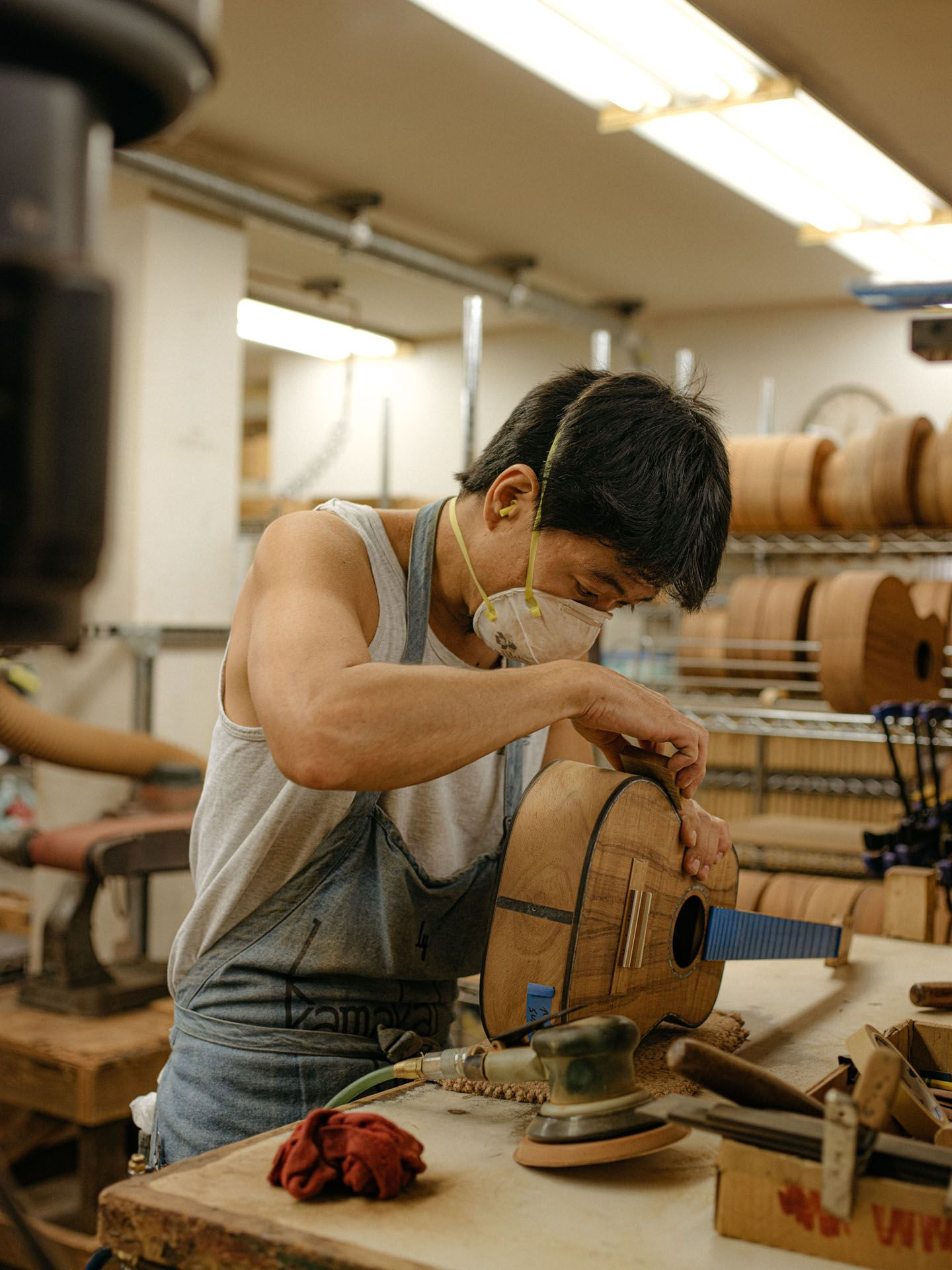 native hawaiian guitar maker working in his shop wearing mask by Alexi Hobbs in Hawai'i for enRoute Magazine