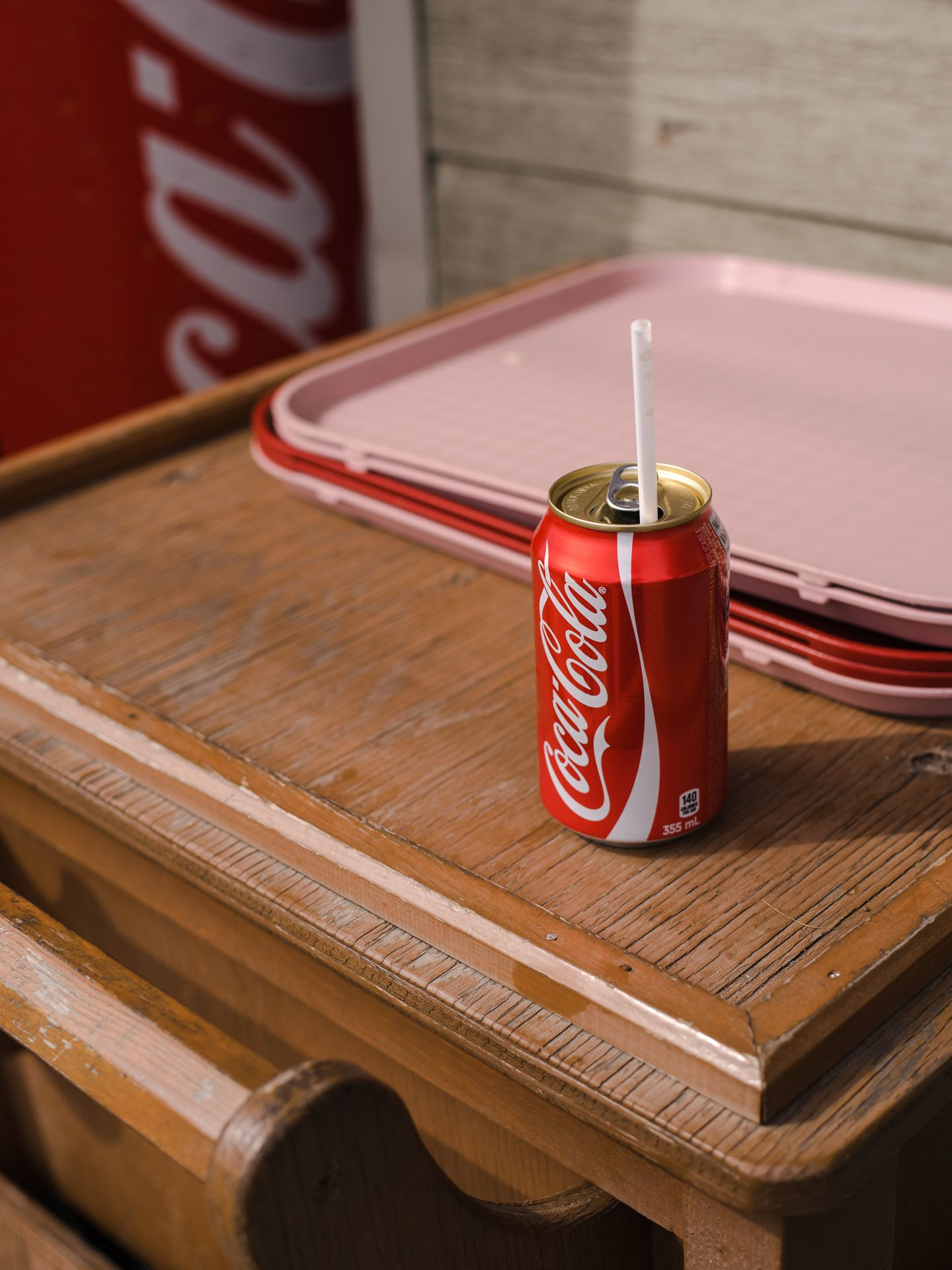 can of coca-cola with plastic straw next to dirty light pink trays atop trash by Alexi Hobbs in St-Tite for Larose Paris