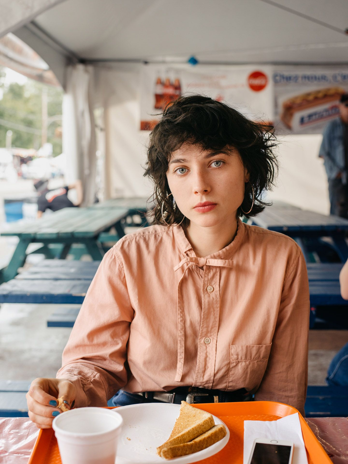 female model black hair blue eyes looking at camera wearing old pink shirt with blue jeans sitting in front of plate of toast by Alexi Hobbs in St-Tite for LArose Paris