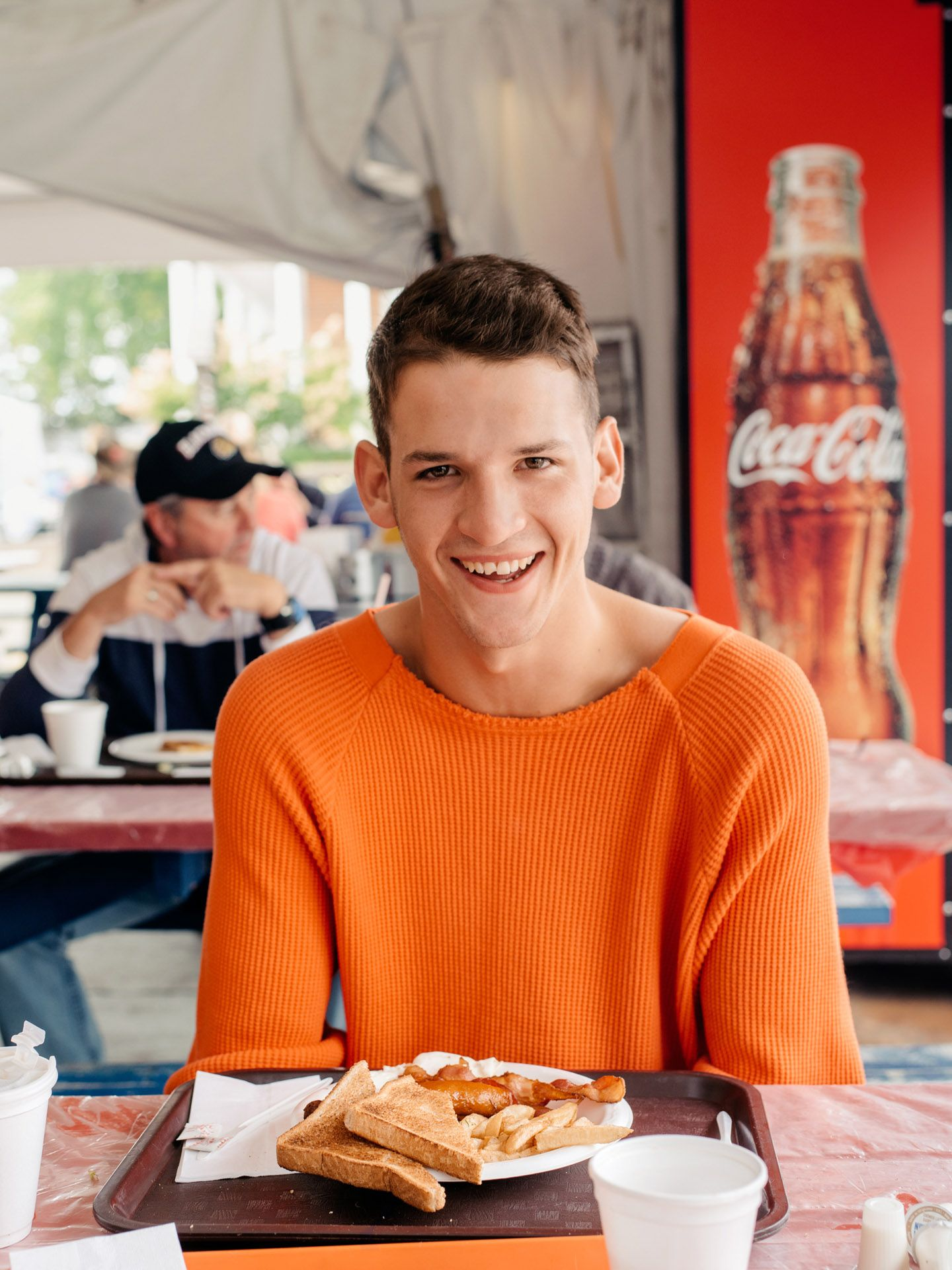 male model looking at camera smiling wearing bright orange sweater sitting in front of plate of toast potatoes sausages by Alexi Hobbs in St-Tite for Larose Paris