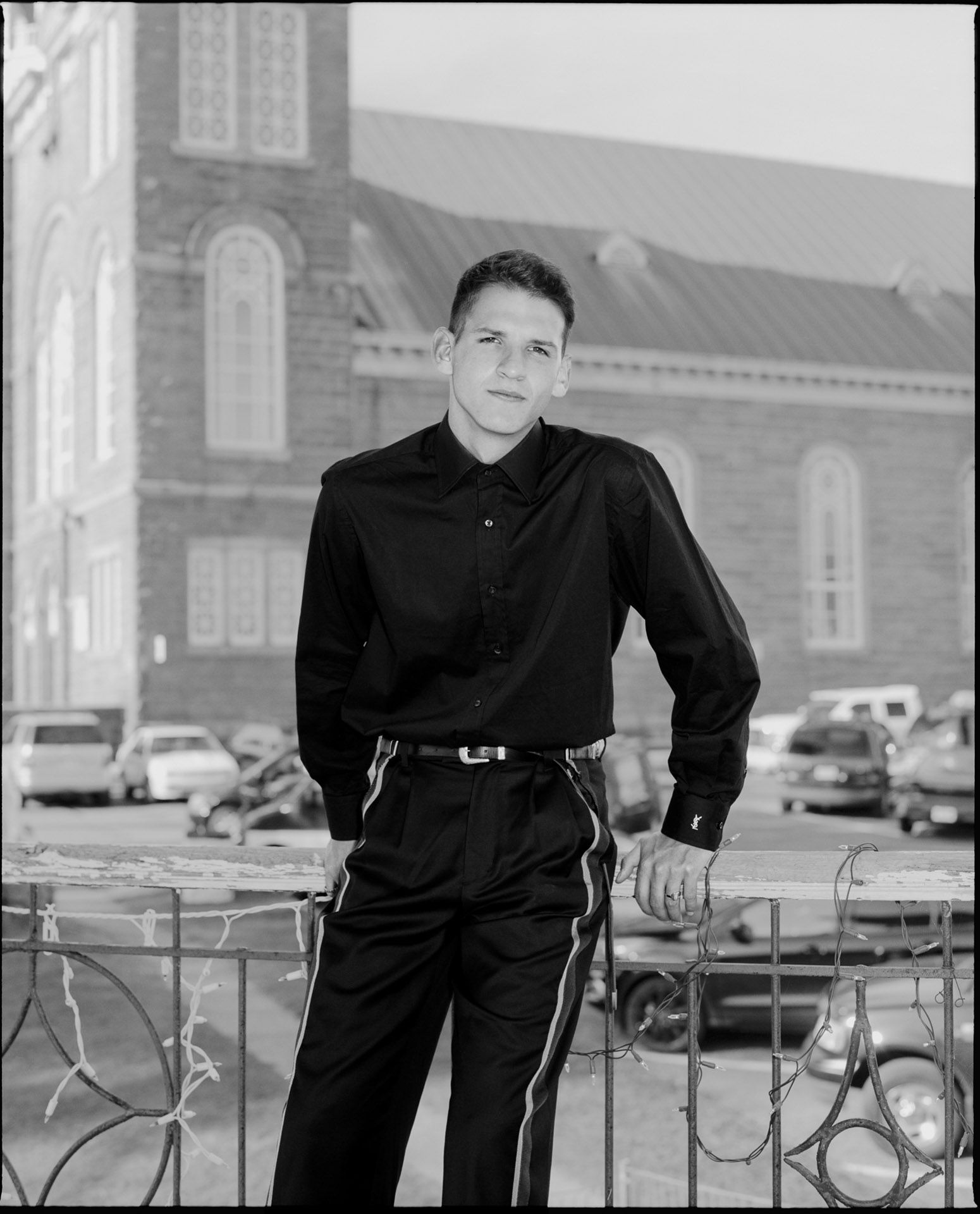male model leaning against railing wearing nice black shirt and black jeans by Alexi Hobbs in St-Tite for Larose Paris