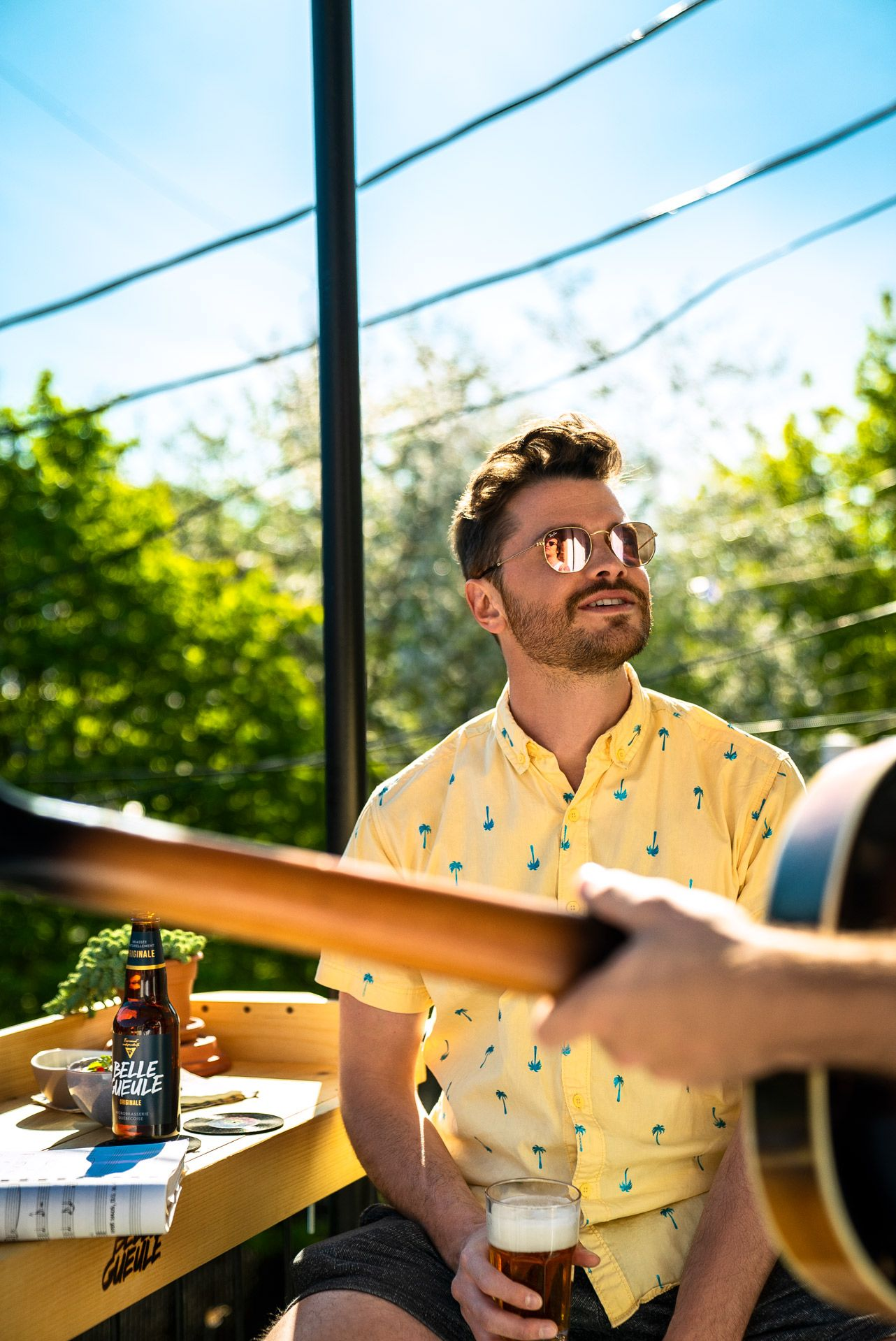 bearded man holding glass of beer in his hand laughing wearing yellow shirt patterned with blue palm trees sitting next to balcony bar attachment photographed by Bruno Florin for Belle Gueule with Forsman & Bodenfors