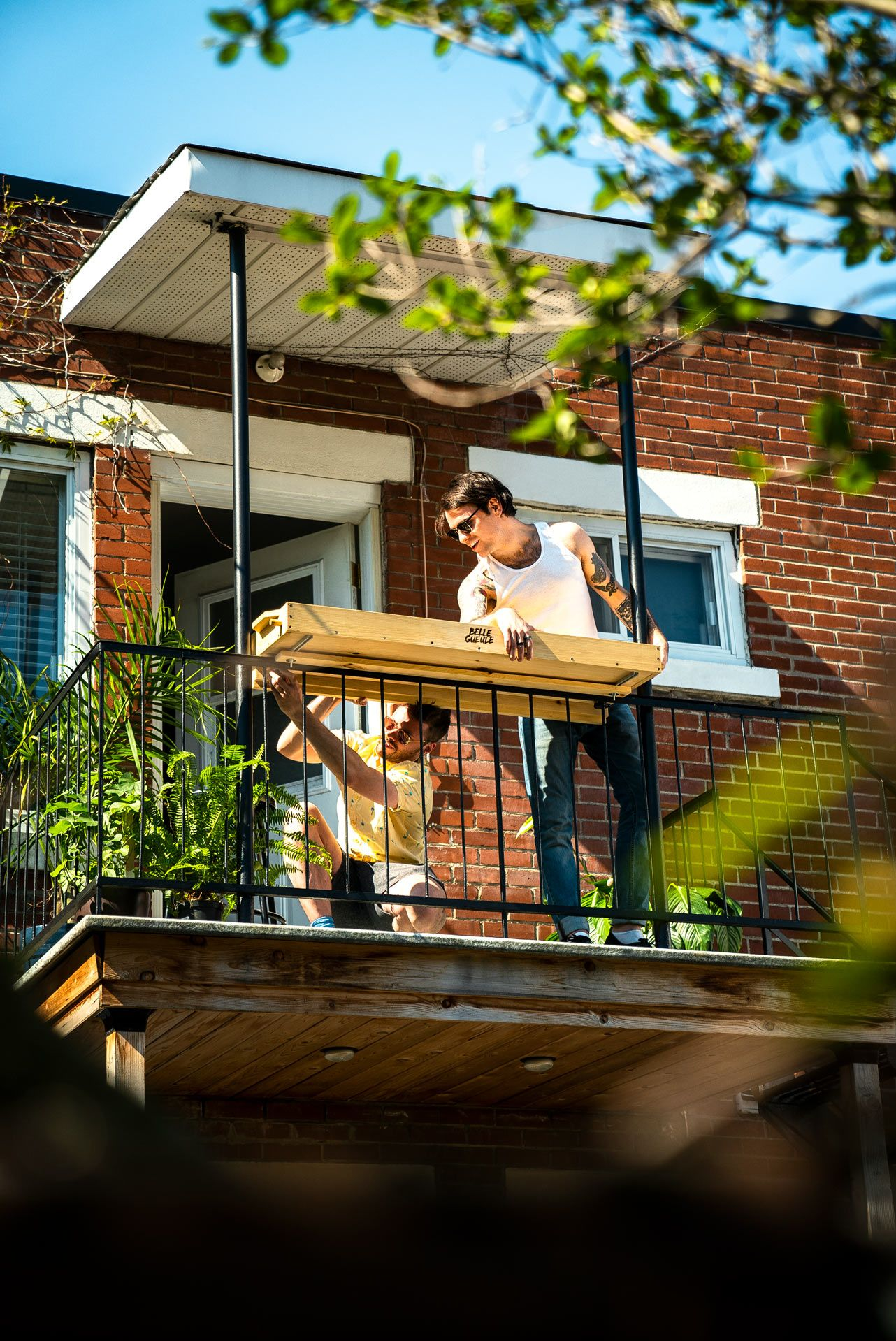 two man installing their balcony bar attachment by Belle Gueule and laughing photographed by Bruno Florin for Belle Gueule with Forsman & Bodenfors