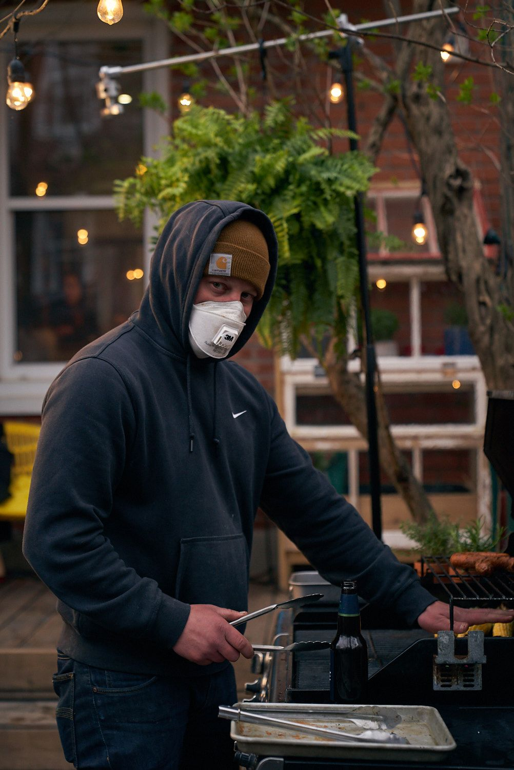 assistant grilling on barbecue while wearing masks in behind the scenes for shoot photographed by Bruno Florin for Belle Gueule with Forsman & Bodenfors