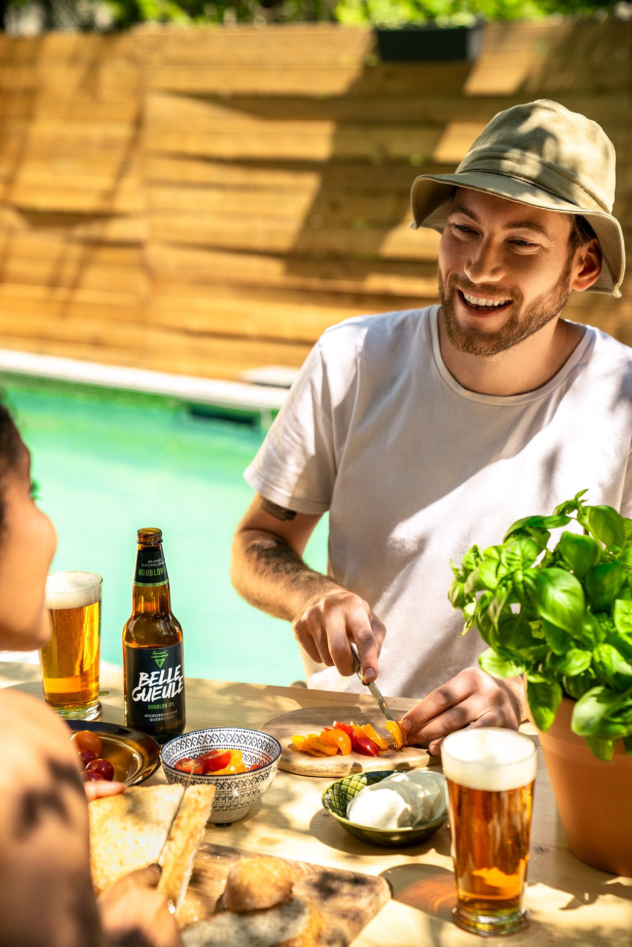 bearded man cutting small tomatoes on table while drinking beer and talking with woman in front of him wearing white shirt and beige bob hat with pool in the background photographed by Bruno Florin for Belle Gueule with Forsman & Bodenfors