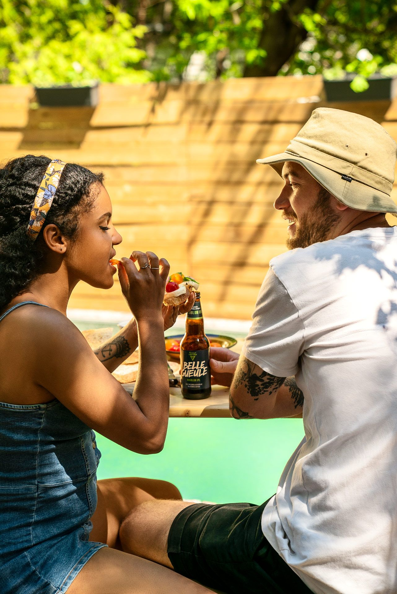 bearded man drinking beer wearing white shirt and beige bob hat and talking with woman sitting next to him wearing jeans overall and eating toast topped with mozzarella and small tomatoes with pool in the background photographed by Bruno Florin for Belle Gueule with Forsman & Bodenfors