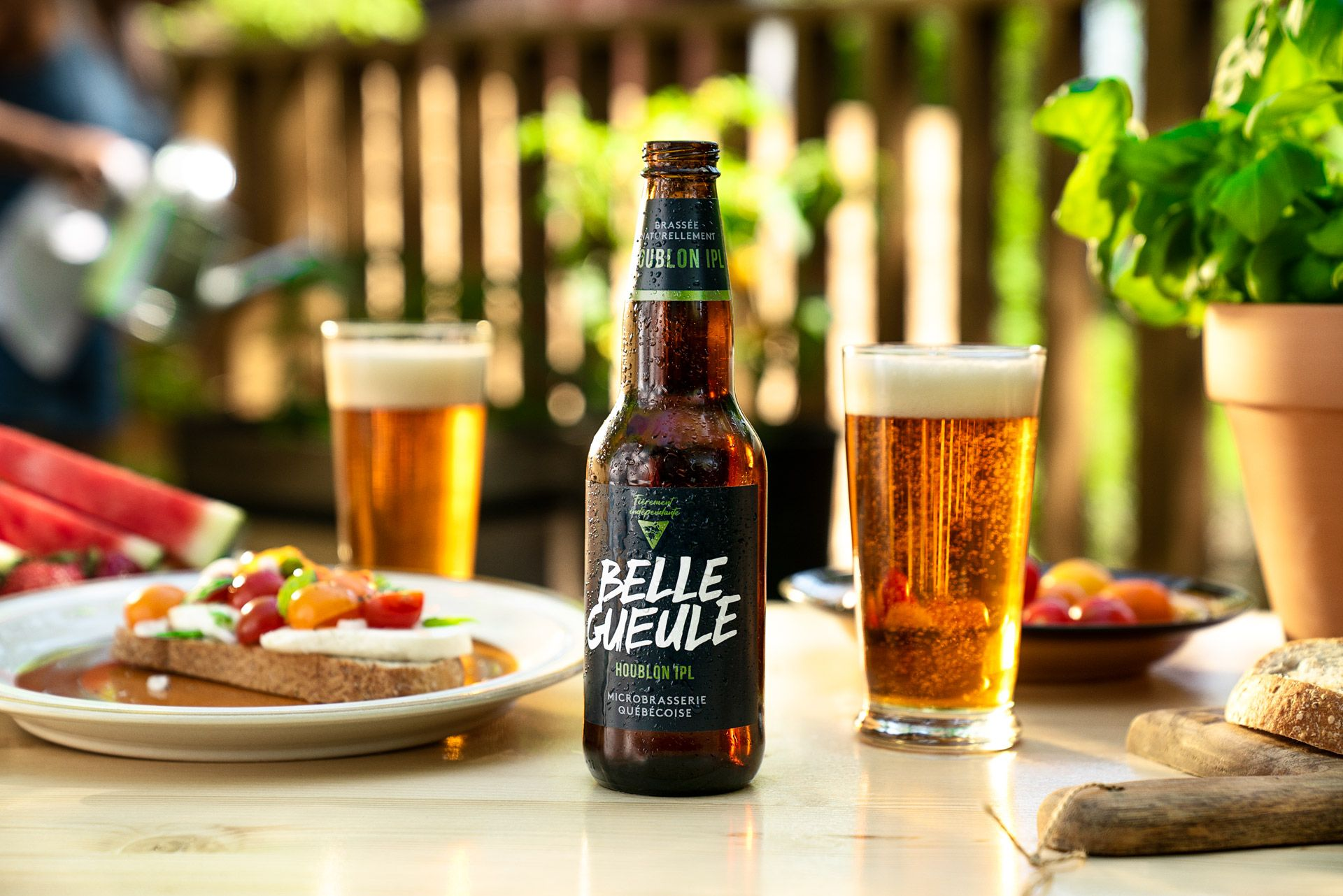 Belle Gueule's houblon IPL beer on table next to two glasses and tomato and feta salad photographed by Bruno Florin for Belle Gueule with Forsman & Bodenfors
