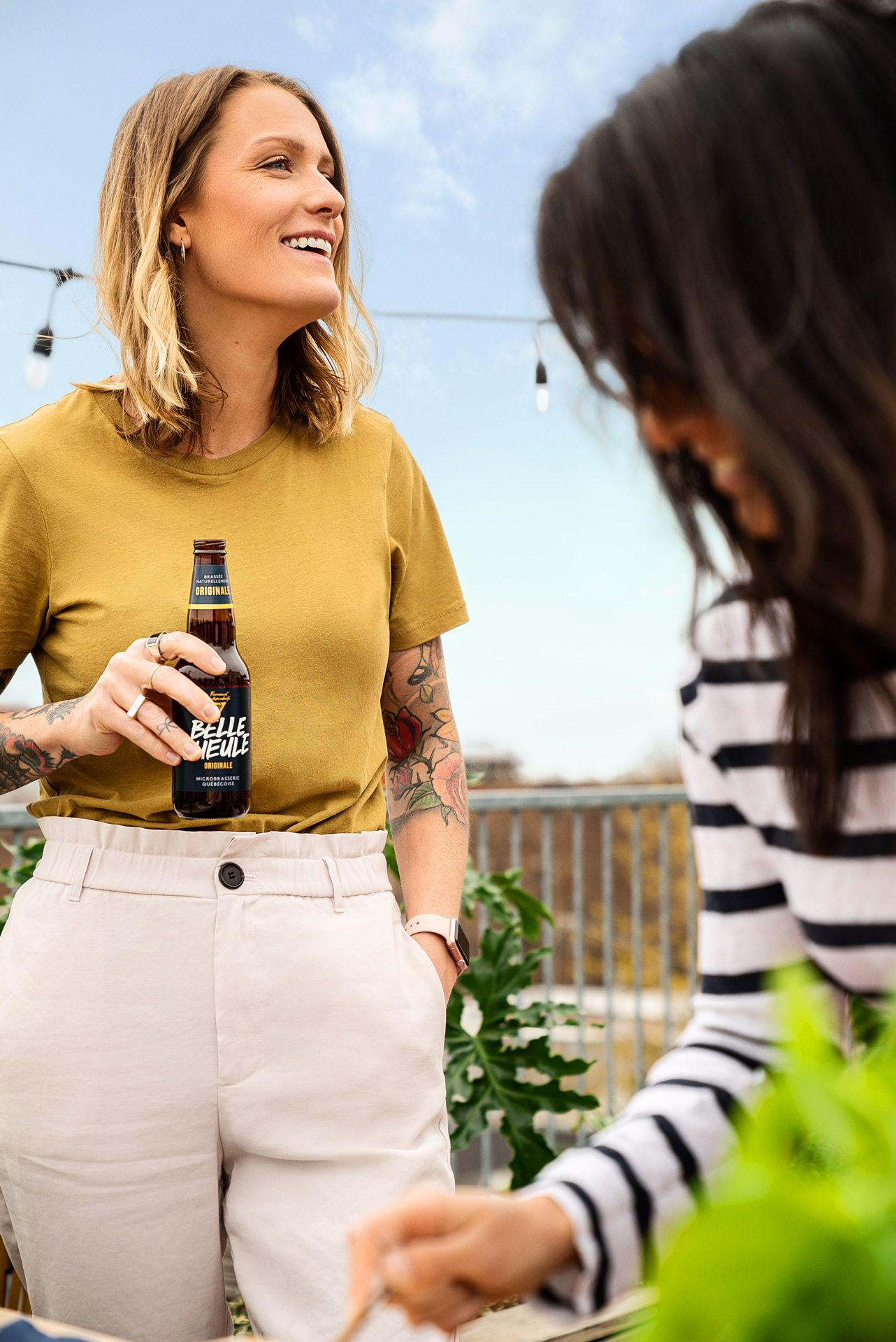blonde woman wearing mustard shirt and beige pants holding Belle Gueule beer in her hand laughing with dark haired woman blurred in the foreground laughing while preparing homemade pizza wearing black and white stripped shirt photographed by Bruno Florin for Belle Gueule with Forsman & Bodenfors