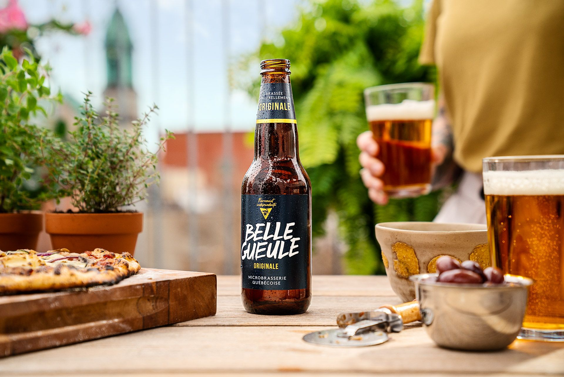 Belle Gueule's original beer on table next to homemade pizza photographed by Bruno Florin for Belle Gueule with Forsman & Bodenfors