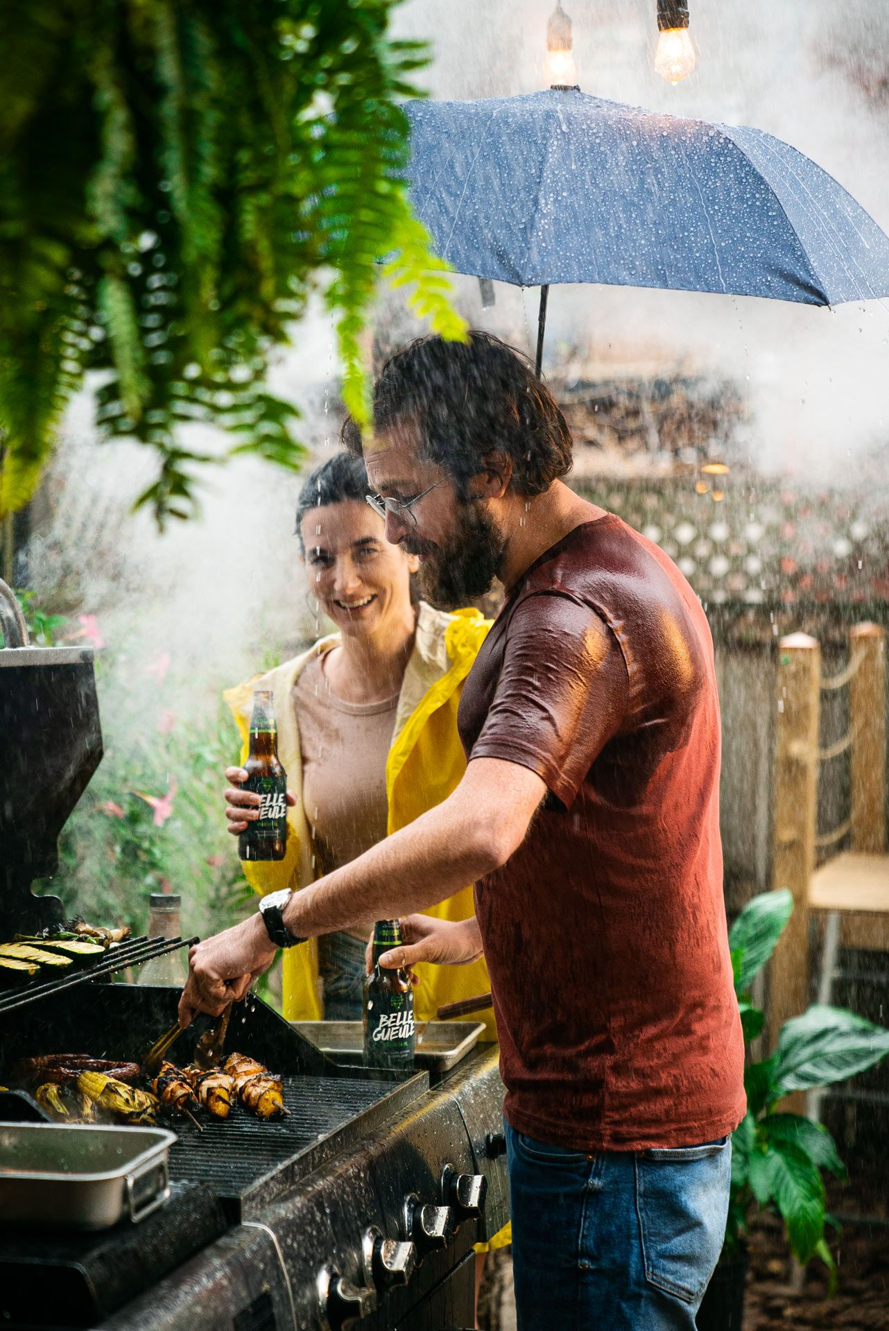 bearded man grilling in front of barbecue in the rain wearing blue jeans and wet red shirt half-protected by umbrella held by woman wearing yellow raincoat photographed by Bruno Florin for Belle Gueule with Forsman & Bodenfors