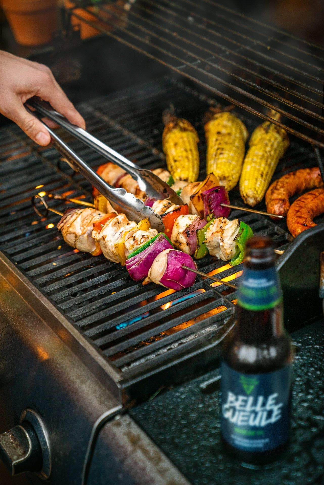 man grilling on barbecue turning chicken skewers with Belle Gueule beer in the foreground photographed by Bruno Florin for Belle Gueule with Forsman & Bodenfors