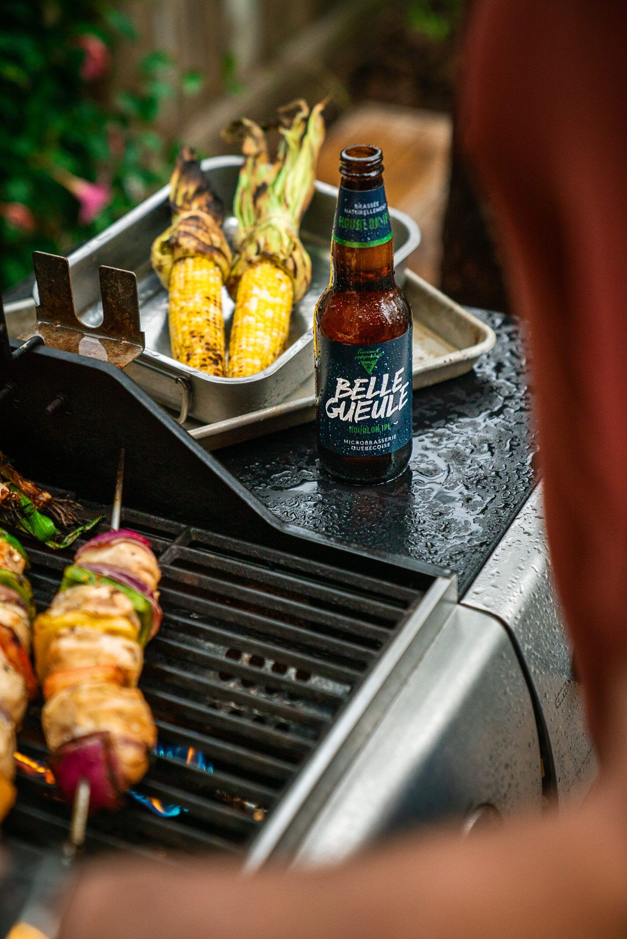 man grilling on barbecue turning chicken skewers with Belle Gueule beer and grilled corn cobs in the center photographed by Bruno Florin for Belle Gueule with Forsman & Bodenfors