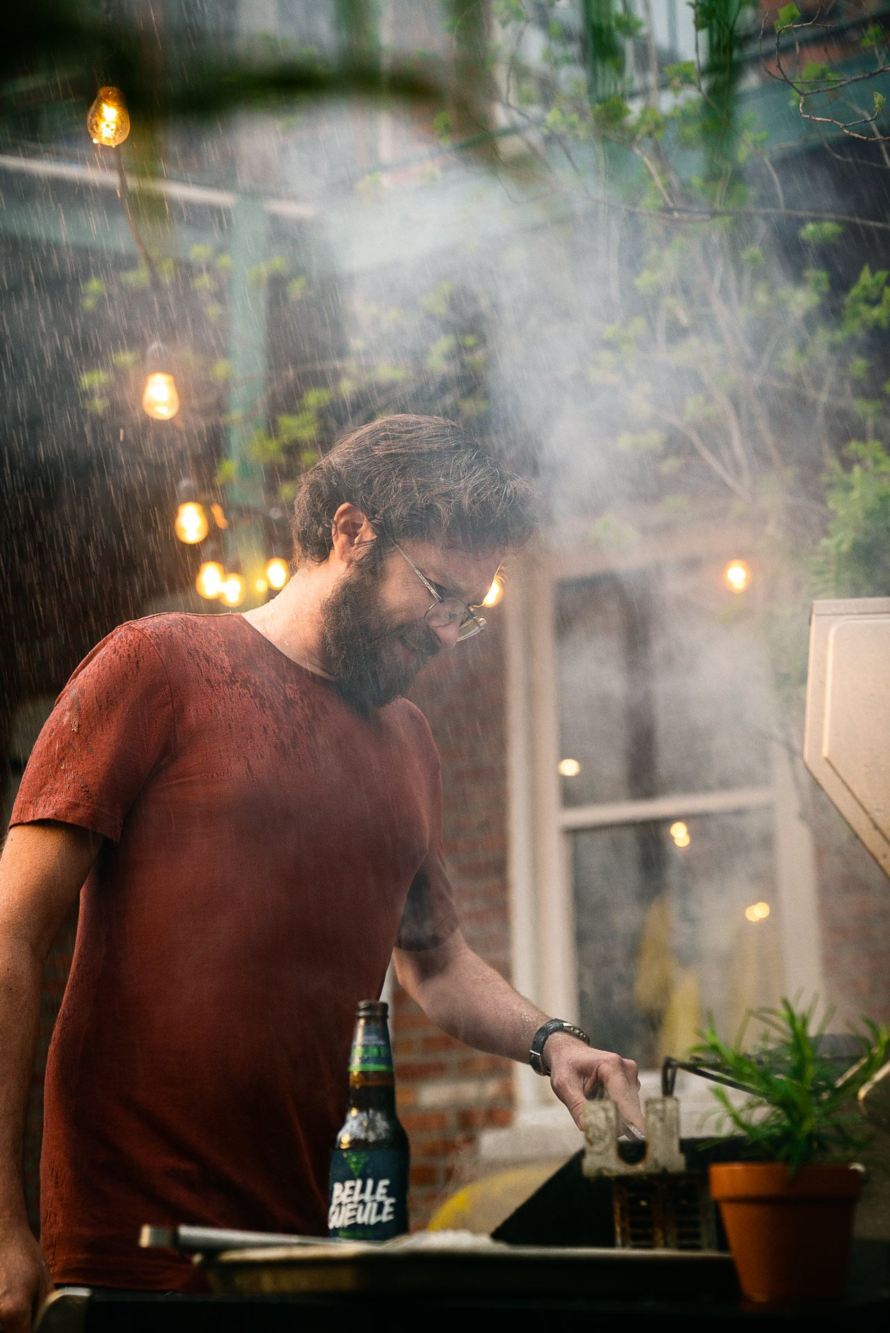 bearded man grilling in front of barbecue in the rain wearing blue jeans and wet red shirt with Belle Gueule bear next to him photographed by Bruno Florin for Belle Gueule with Forsman & Bodenfors