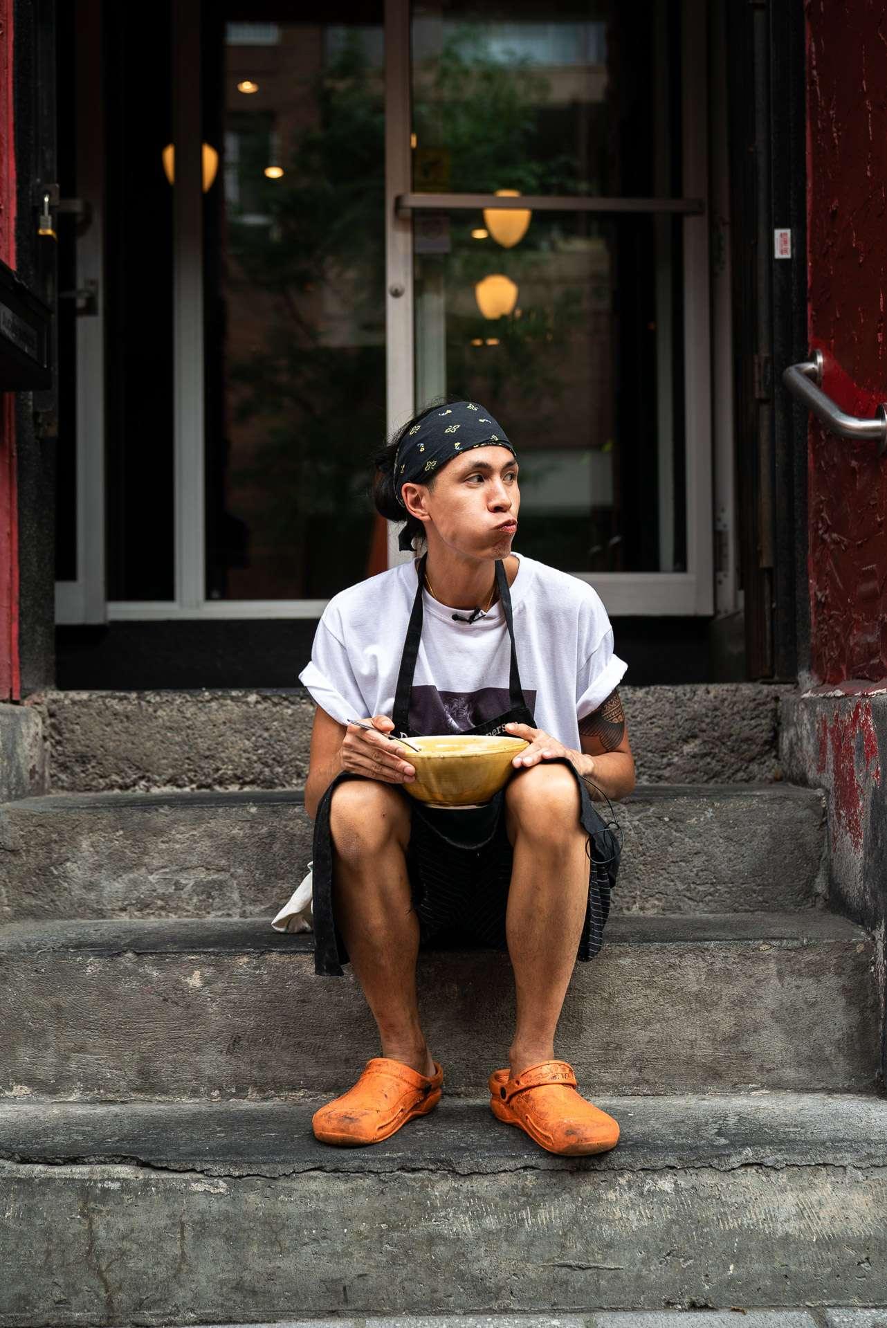 portrait du chef Minh Phat Tu mangeant son plat d'enfance devant son restaurant l'Orange Rouge par Bruno Florin