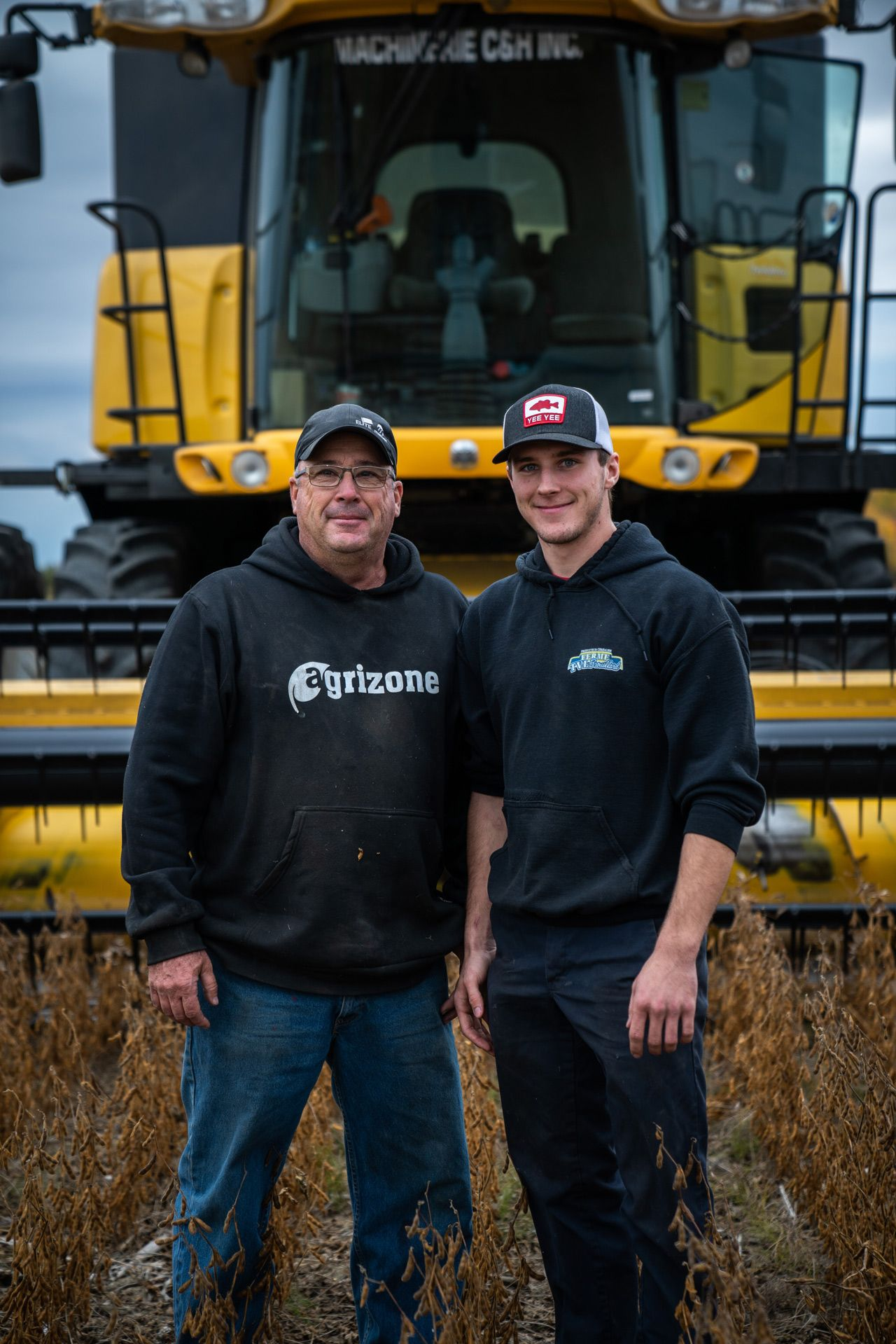 father and son in the field in front of heavy machinery smiling by Bruno Florin for Sollio Agriculture