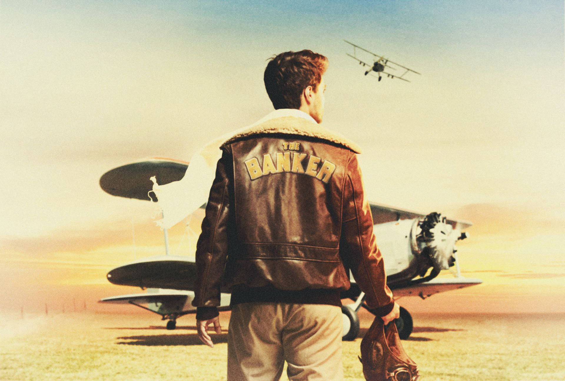 """man from back walking towards airplane in desert wearing brown leather jacket with """"The Banker"""" written on the back photographed by Simon Duhamel for bank BNP Paribas"""