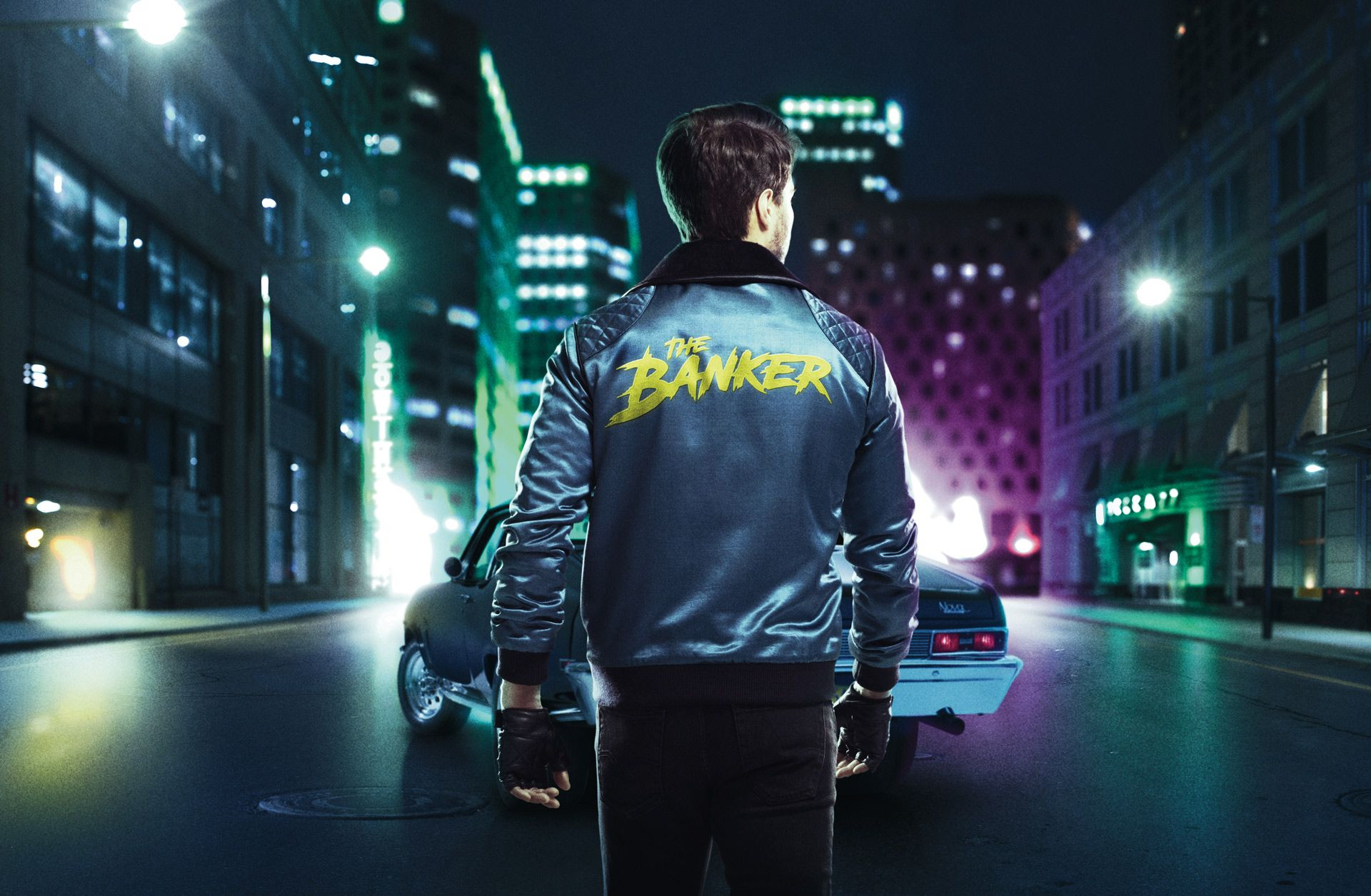 """man from back walking towards car in colored lighting wearing leather jacket with """"The Banker"""" written on the back photographed by Simon Duhamel for bank BNP Paribas"""