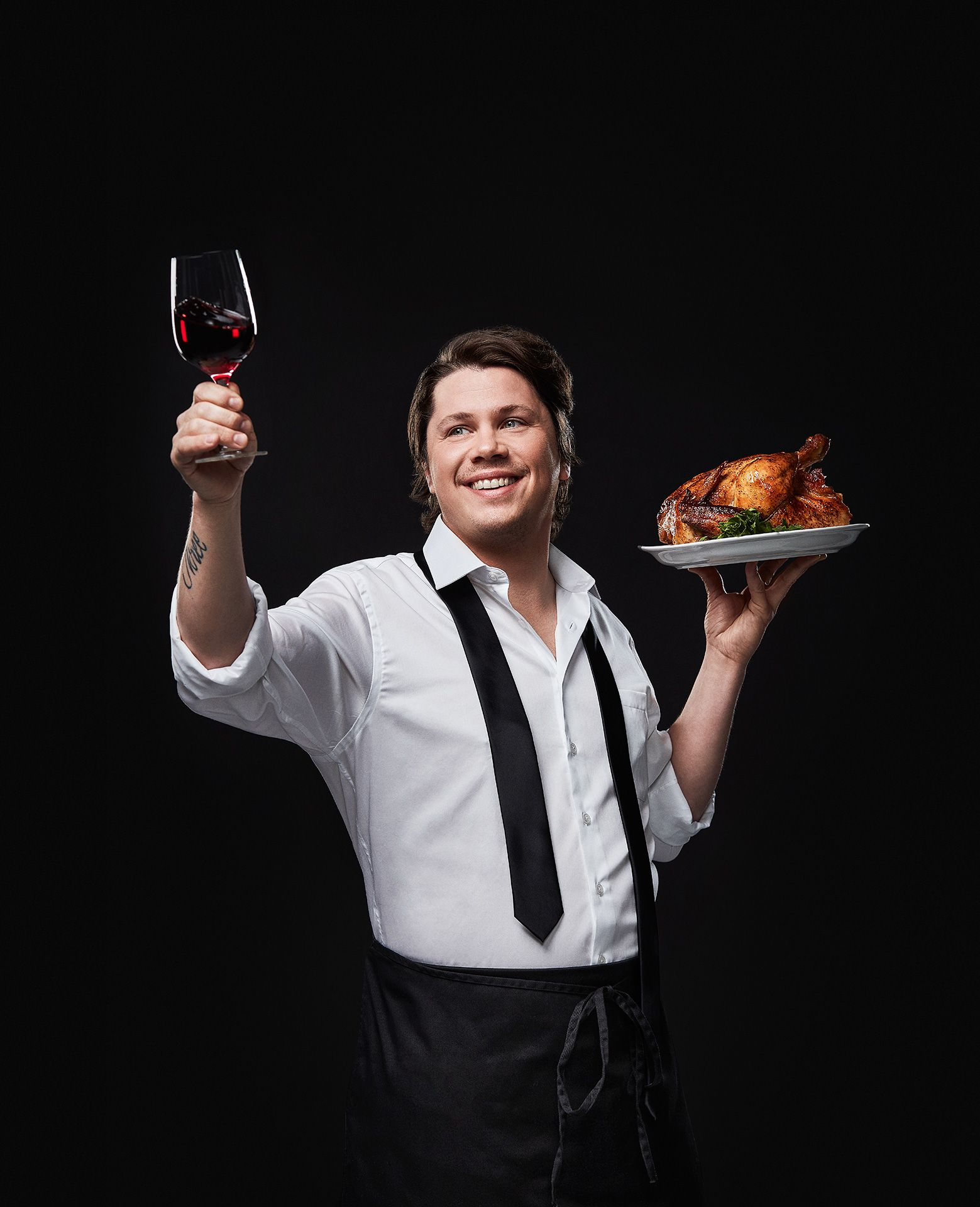 portrait of male chef Nicholas Giambattisto holding a glass of red wine in the air in one hand and a full roasted chicken on a plate in the other by Jocelyn Michel for the Cathcart