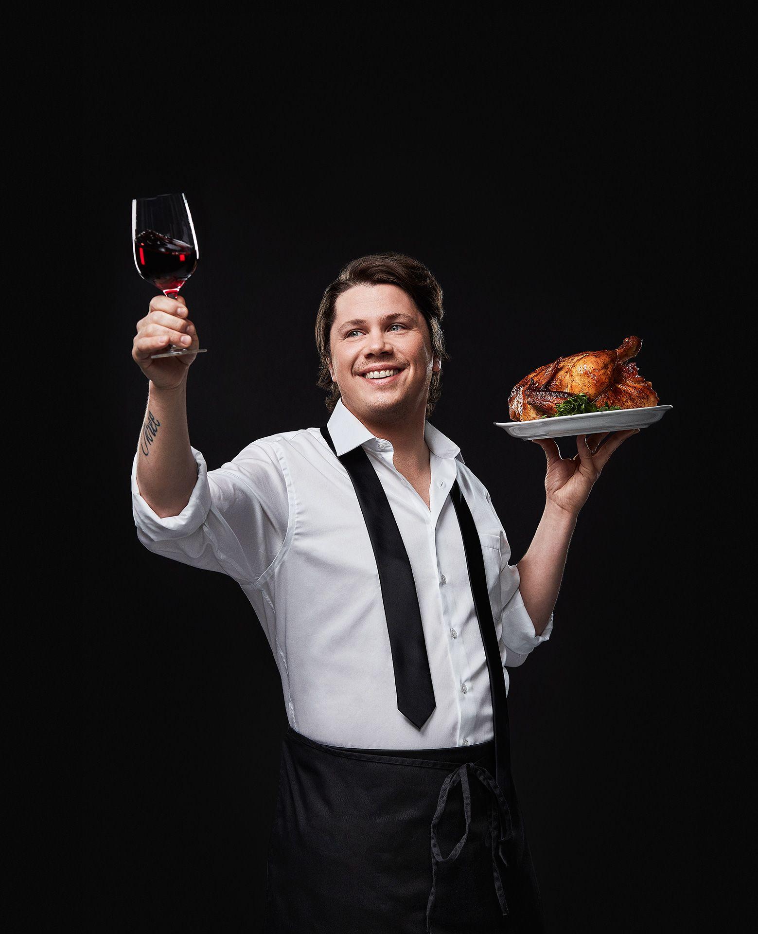 portrait du chef Nicholas Giambattisto levant un verre de vin rouge dans une main et tenant un poulet roti sur une assiette de l'autre par Jocelyn Michel pour le Cathcart