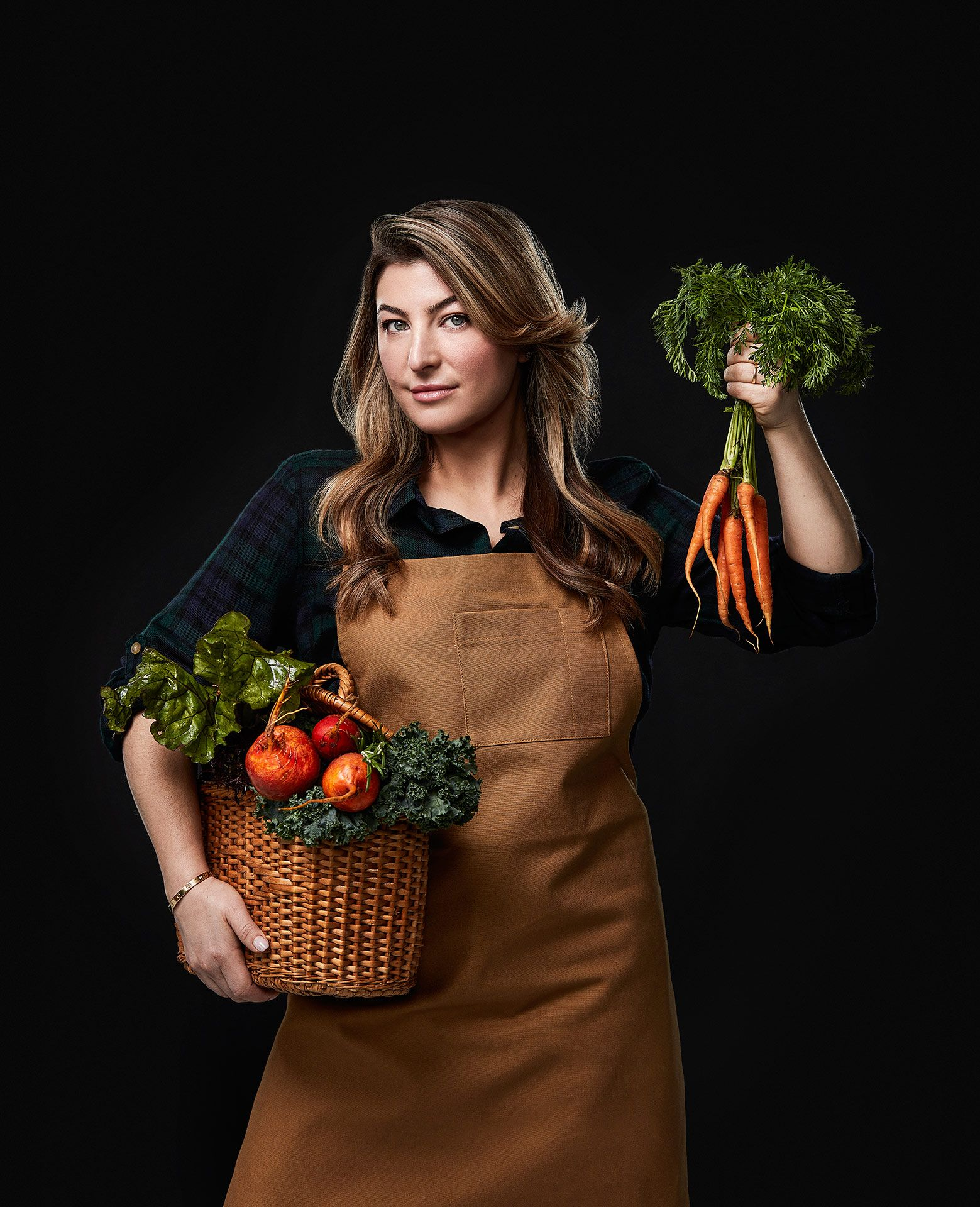 portrait of female chief Reagan Steinberg holding a wicker basket of greens under her arm and a bunch of carrots in the other hand by Jocelyn Michel for the Cathcart