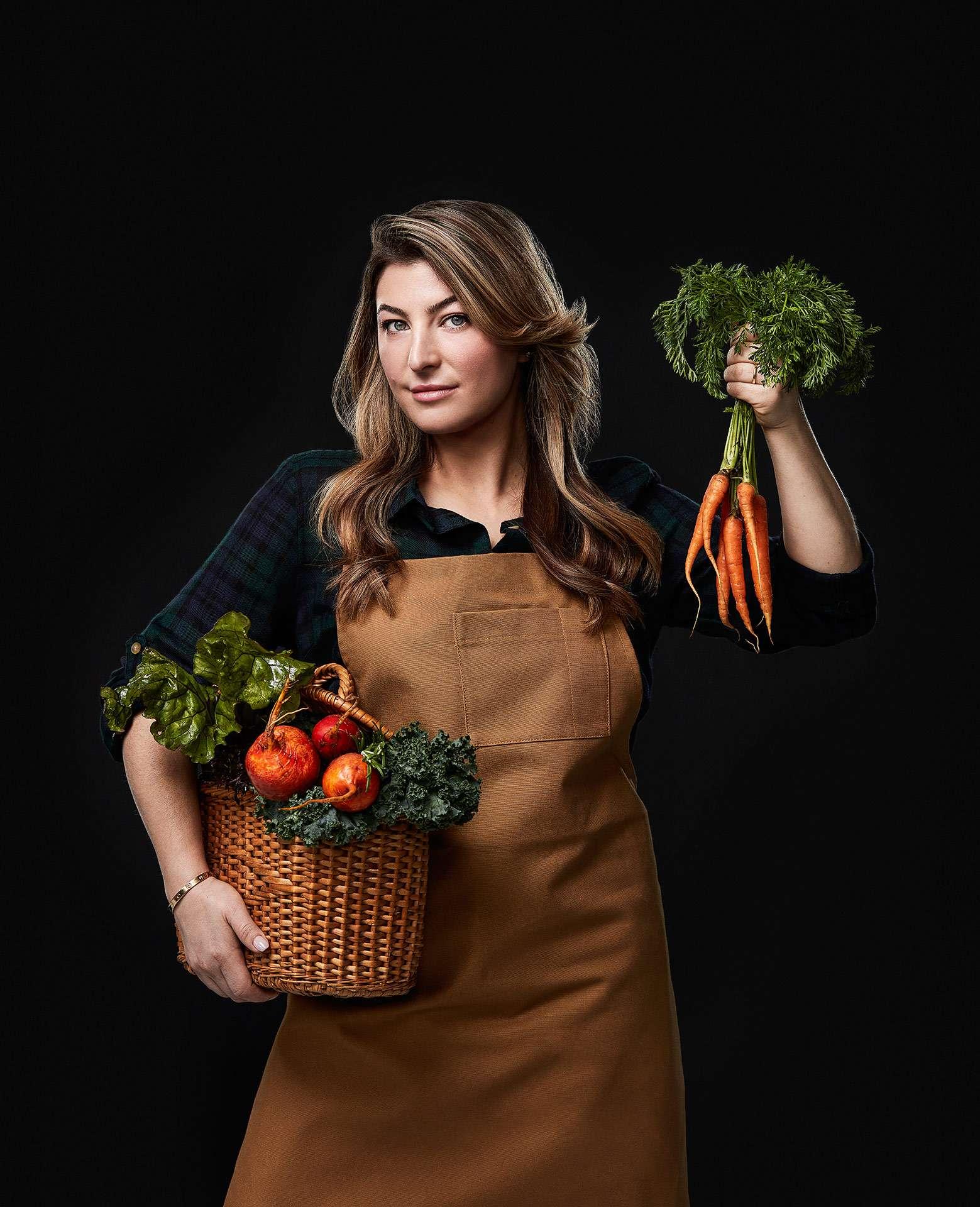 portrait de la chef Reagan Steinberg portant un panier en osier pleins de légumes sous un bras et tenant une botte de carotte dans l'autre main par Jocelyn Michel pour le Cathcart