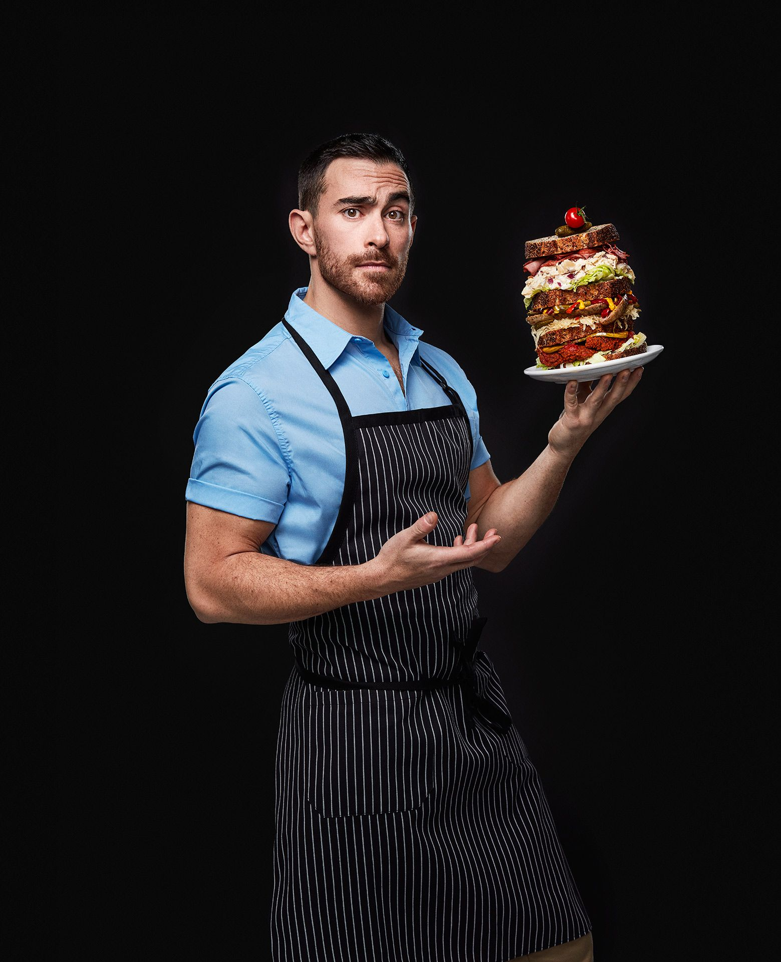 portrait of chief Alex Cohen holding a multi-layered sandwich almost falling over by Jocelyn Michel for the Cathcart