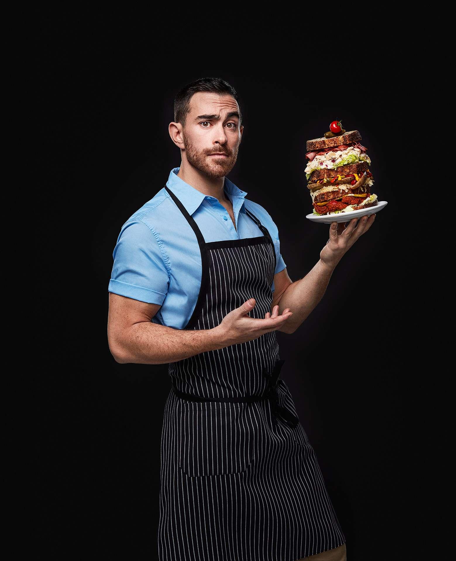 portrait du chef Alex Cohen avec un sandwich à plusieurs étages sur le point de tomber par Jocelyn Michel pour le Cathcart