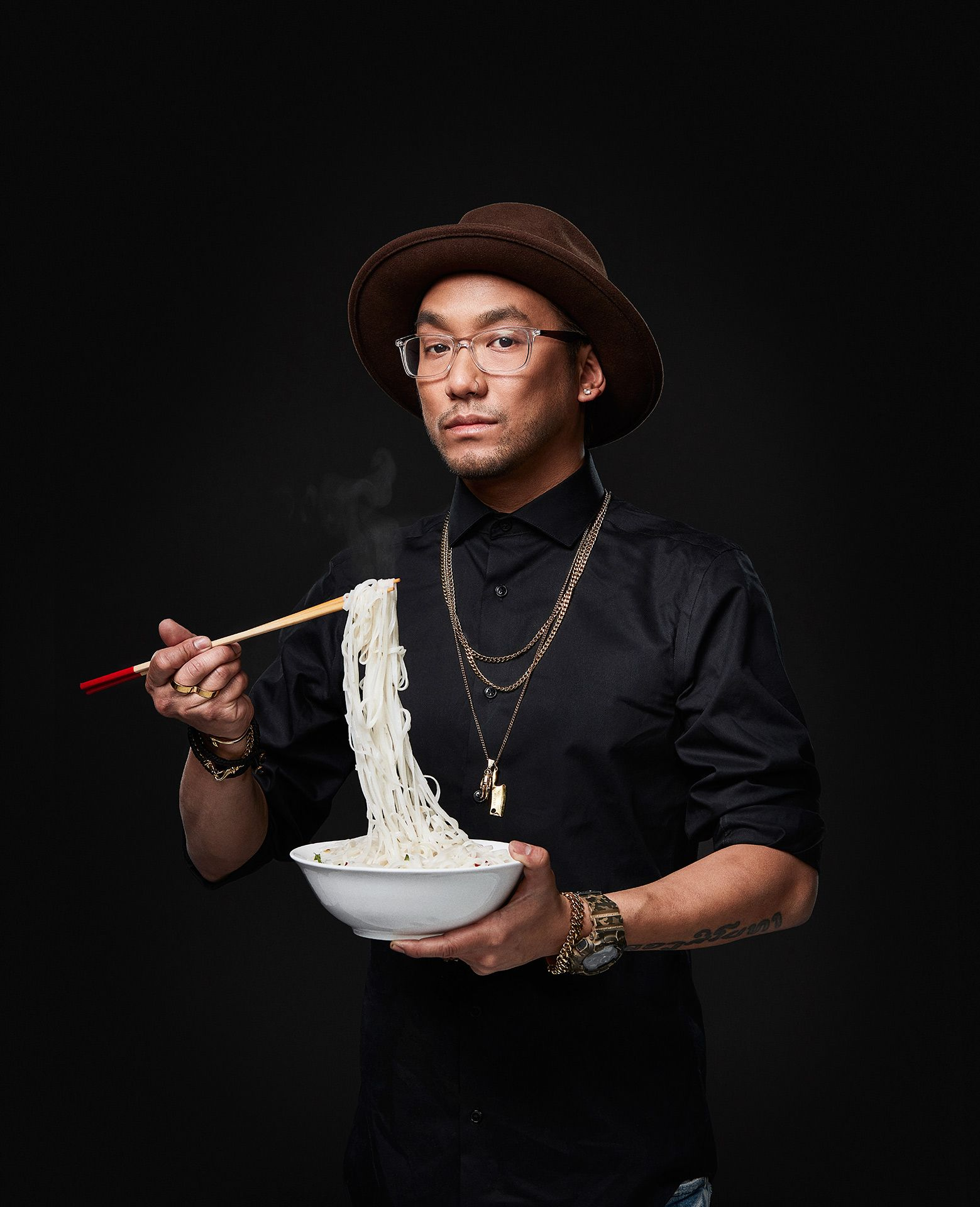 portrait of chef Ross Louangsignotha looking poised wearing jewelry holding chopsticks and a bowl moving rice noodles towards his mouth by Jocelyn Michel for the Cathcart