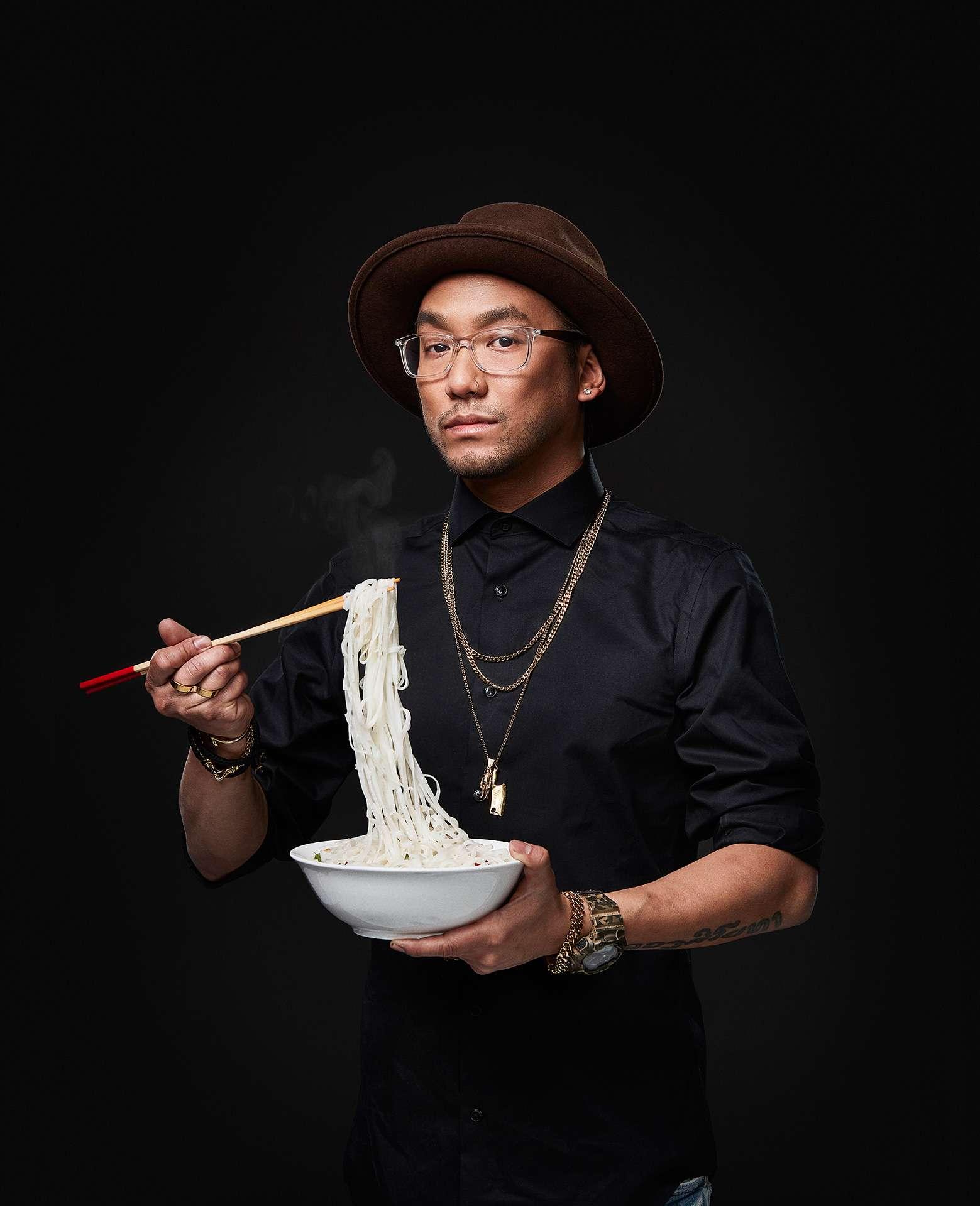 portrait du chef Ross Louangsignotha l'air posé portant des bijoux tenant des baguettes et un bol levant des nouilles de riz vers sa bouche par Jocelyn Michel pour le Cathcart