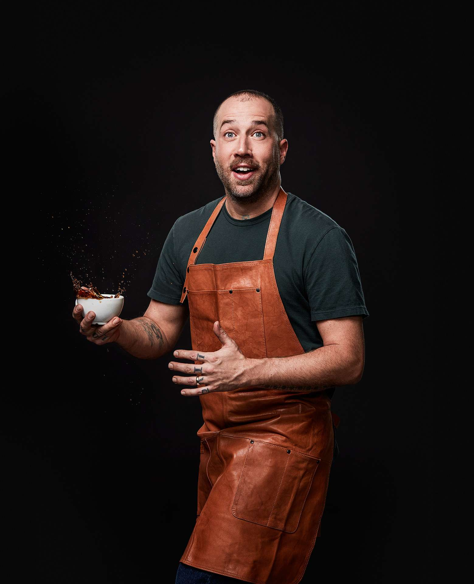 portrait of food stylist and chief Blake Mackay holding a splashing cup of coffee and acting surprised by Jocelyn Michel for the Cathcart