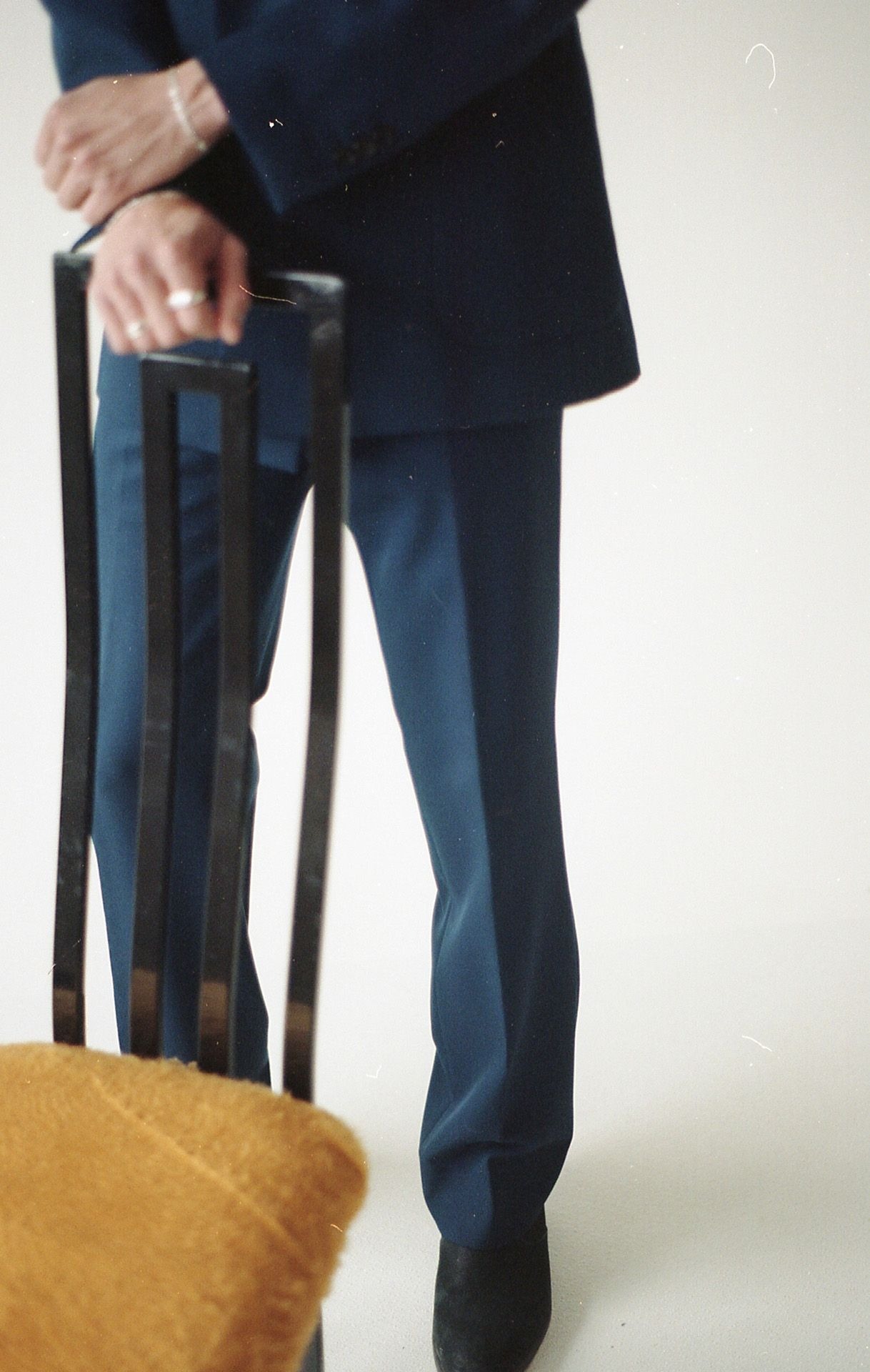male model standing next to designer chair wearing dark blue suit jacket and pants with black heeled shoes for Collector's Cut by Hyperbureau with styling and artistic direction by Studio TB
