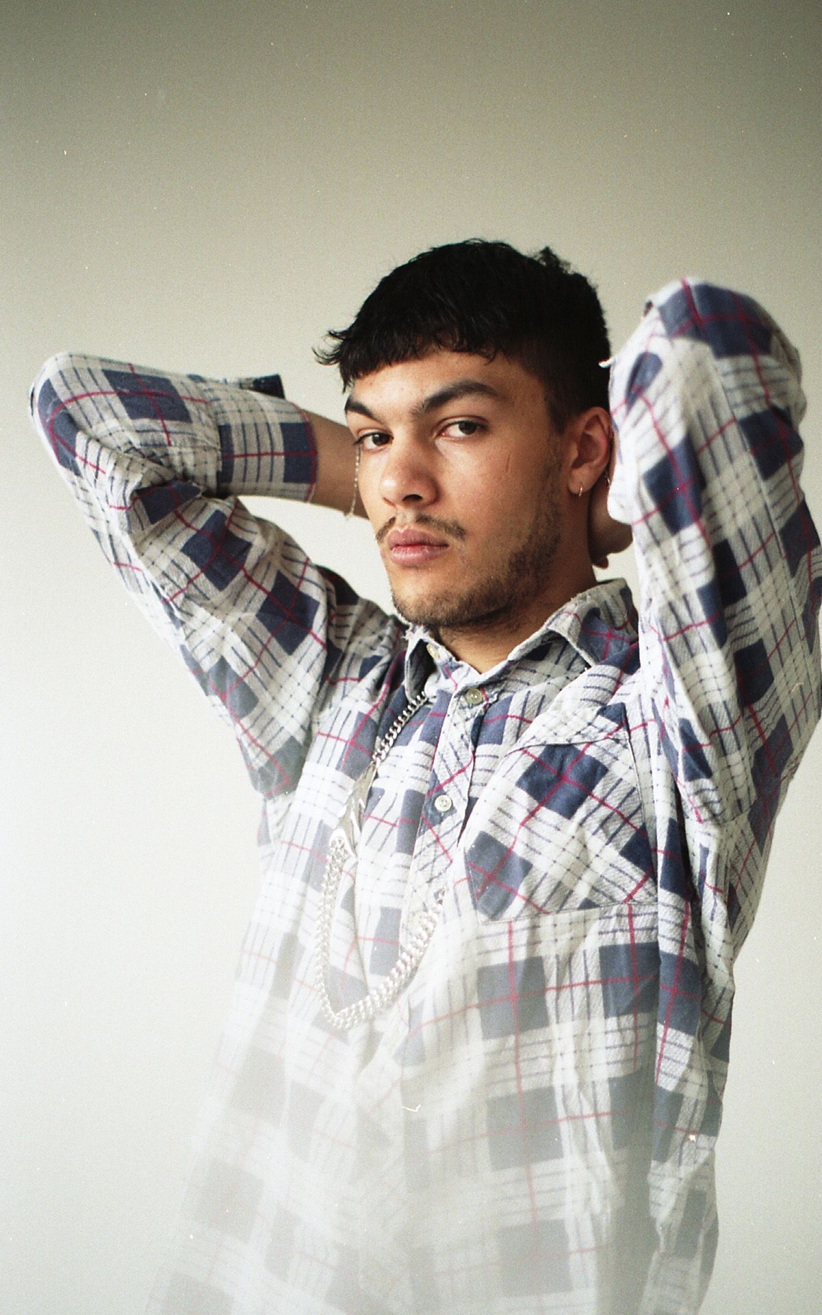 male model arms behind his head wearing dark blue and white checkered flannel looking at camera for Collector's Cut by Hyperbureau with styling and artistic direction by Studio TB
