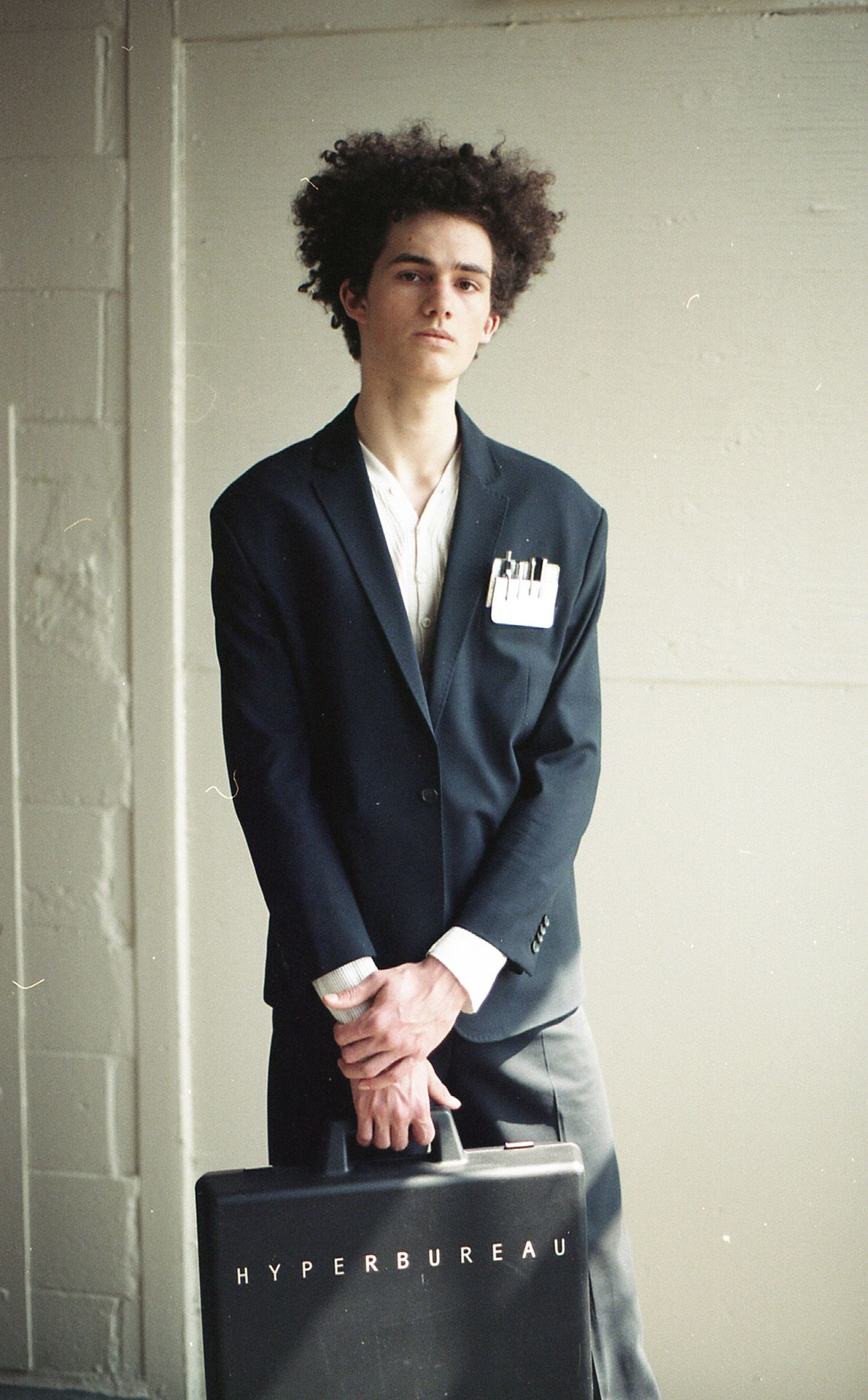 curly haired male model wearing black worksuit jacket and pants holding briefcase branded Hyperbureau looking at camera for Collector's Cut by Hyperbureau with styling and artistic direction by Studio TB