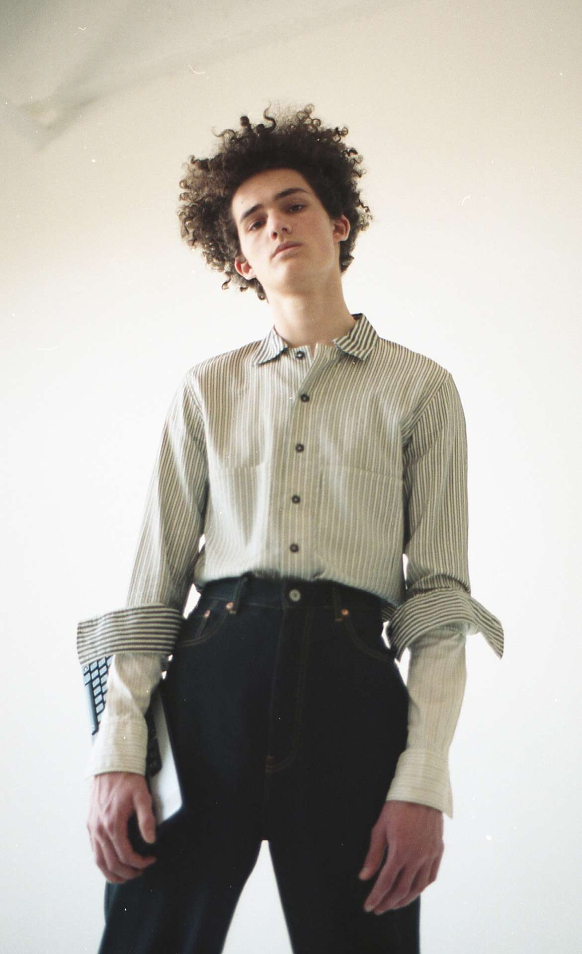 curly haired male model wearing black pants and striped shirt looking at camera for Collector's Cut by Hyperbureau with styling and artistic direction by Studio TB