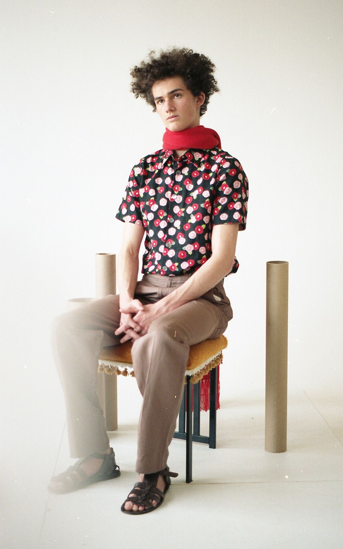 curly haired male model sitting on designer chair wearing black leather spartiate shoes with flower patterned shirt and beige pants and red scarf around his neck for Collector's Cut by Hyperbureau with styling and artistic direction by Studio TB