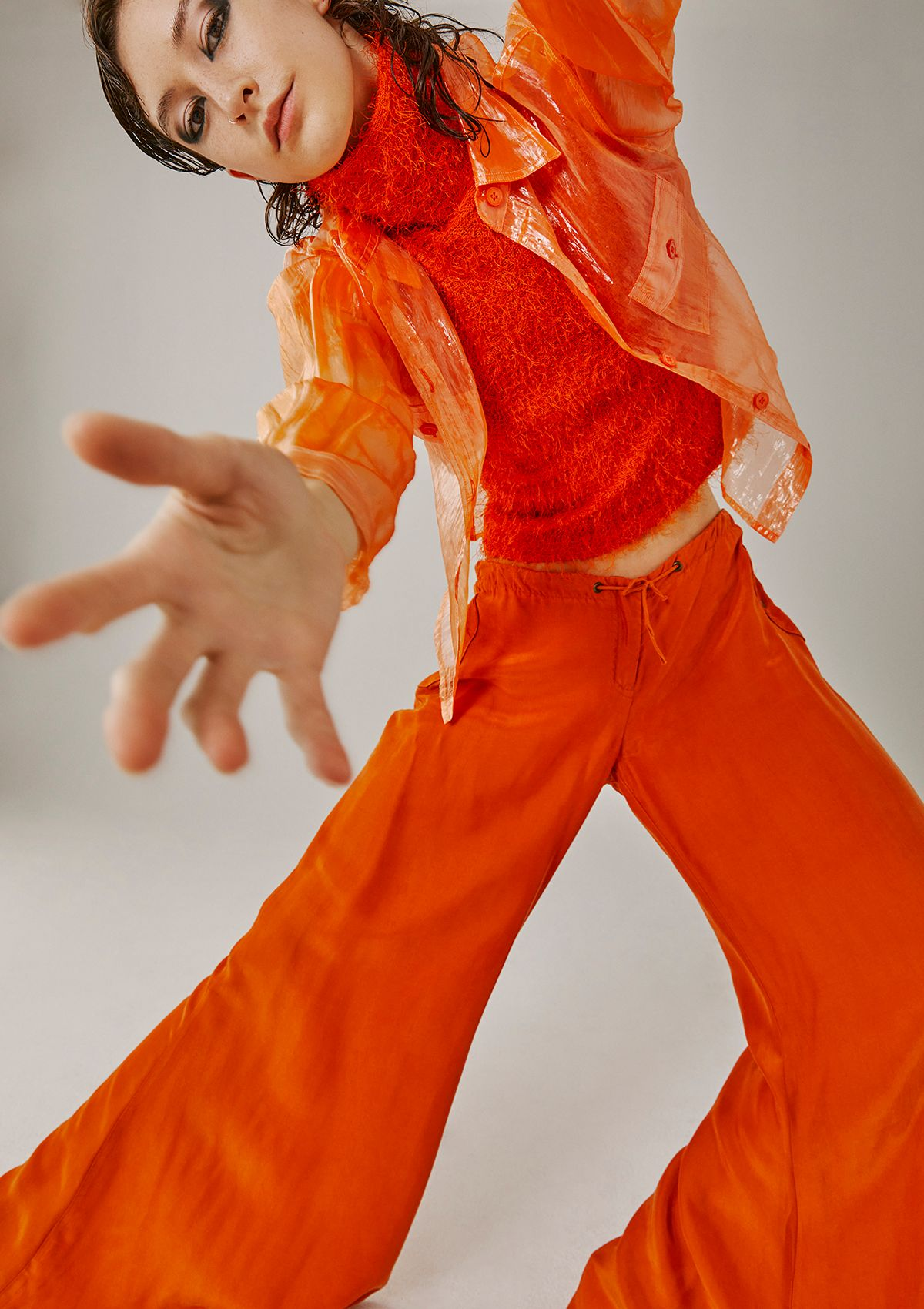 female model all dressed in orange extending hand in front of camera photographed by Kelly Jacob for Editorial for Contributor Magazine