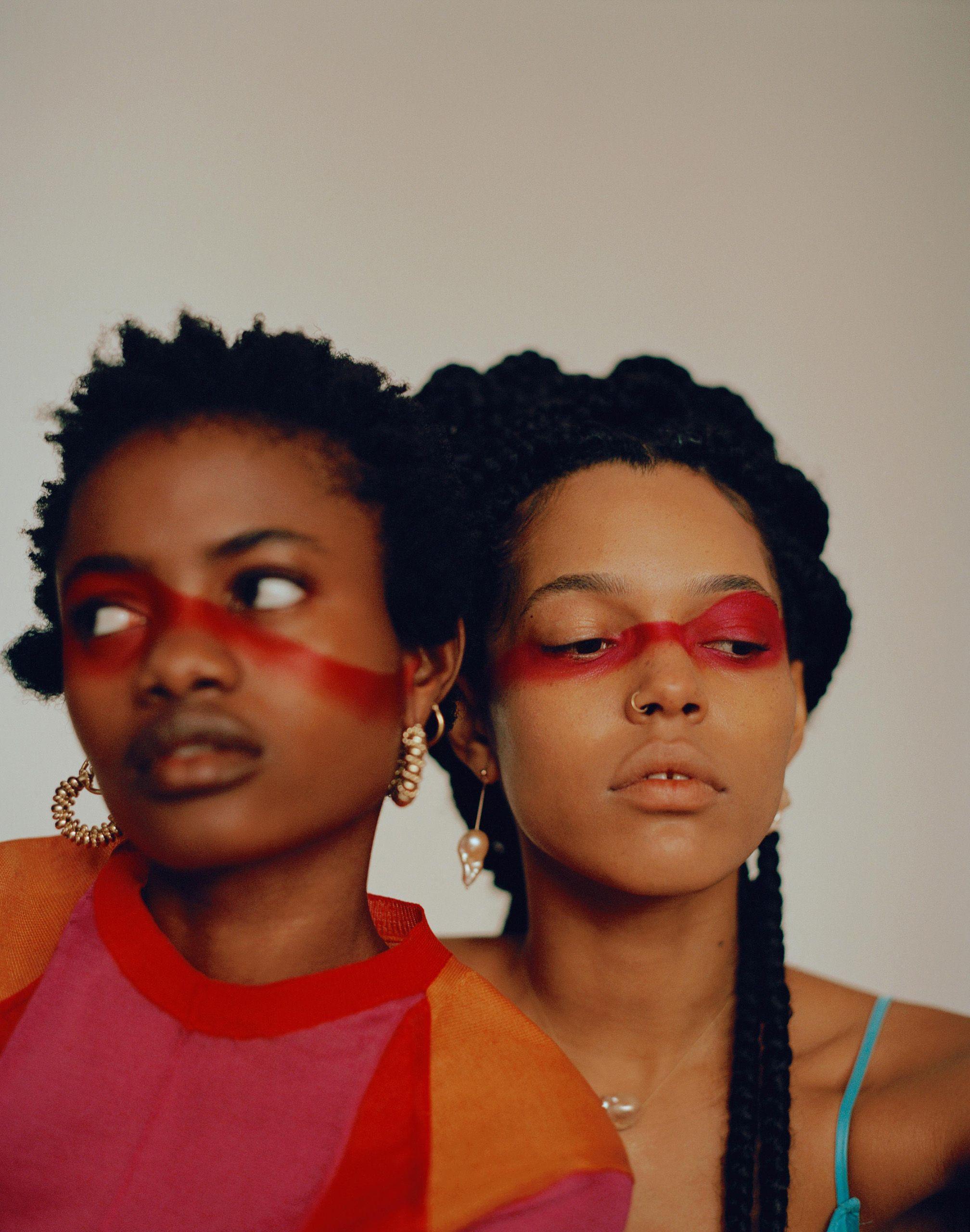 portrait deux femmes assises au sol avec maquillage rouge sur leur visage pour vogue arabia
